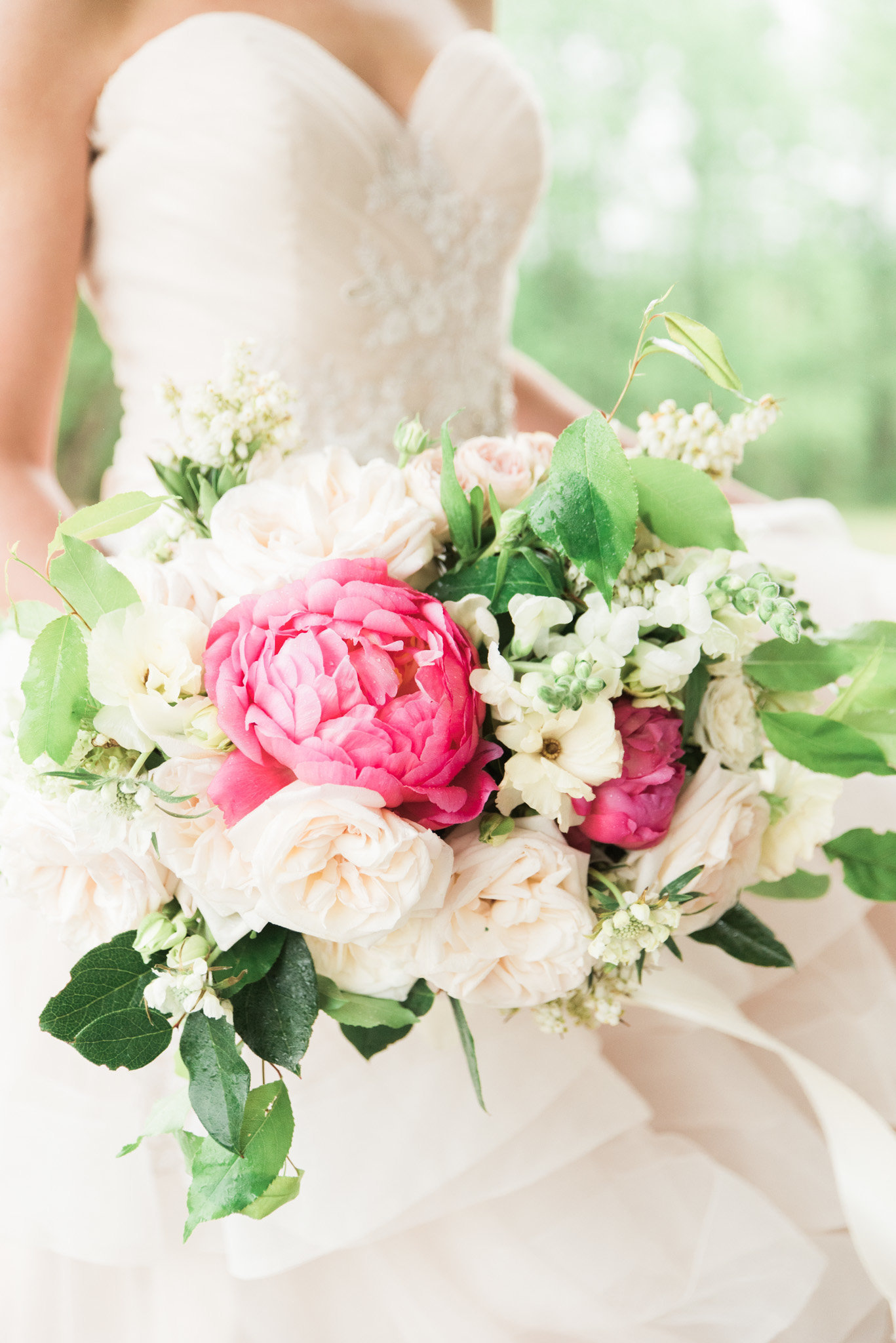 Bride dressed in strapless wedding dress holding pink and white peonies bouquet