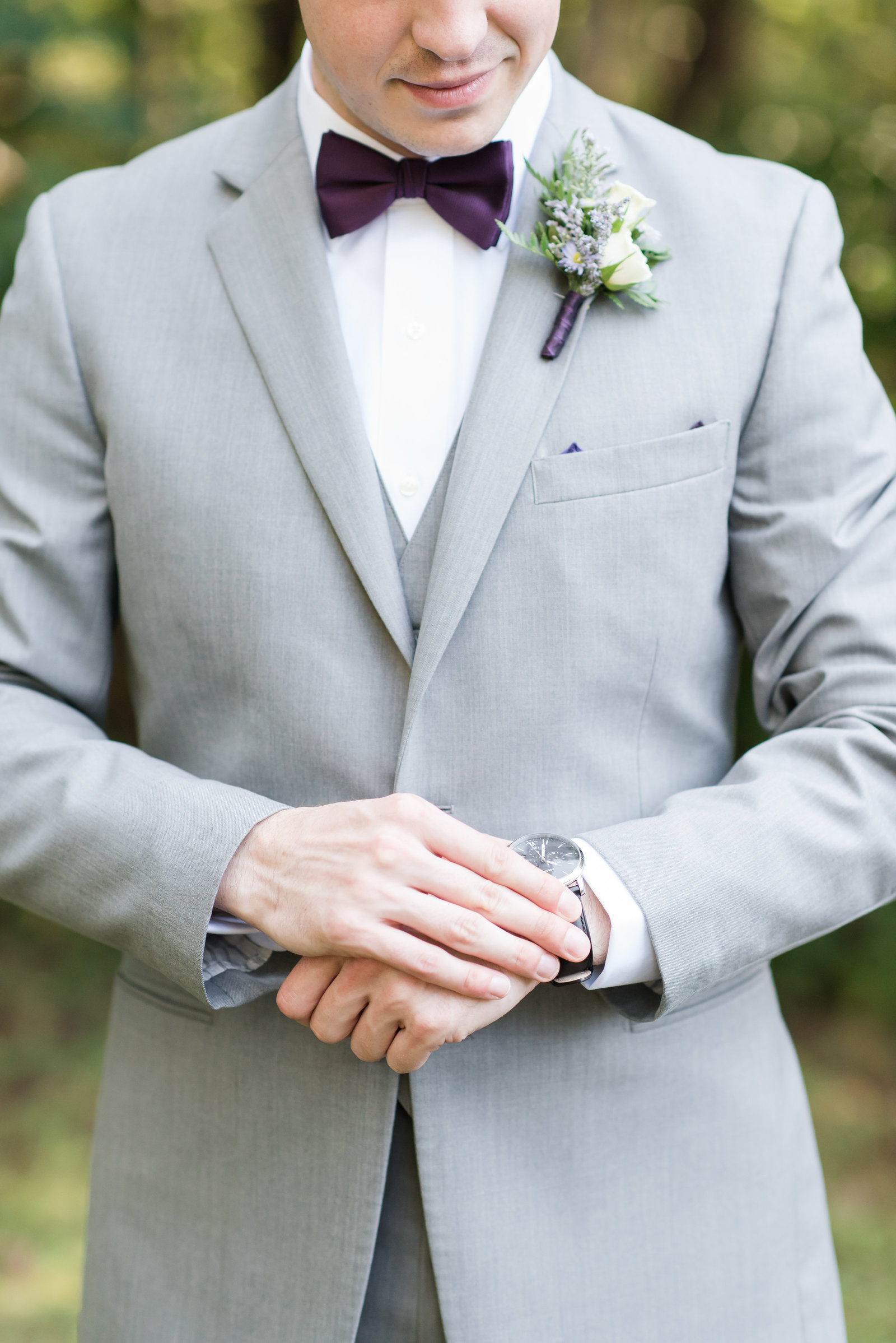 a groom wearing a gray wedding suite with a purple bowtie with while flowers who is looking down fixing his watch at Merry Hill Weddings