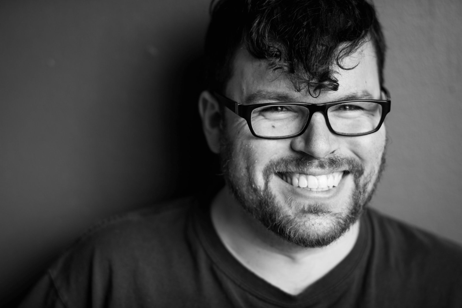 Black and white portrait of smiling, bearded man with glasses.