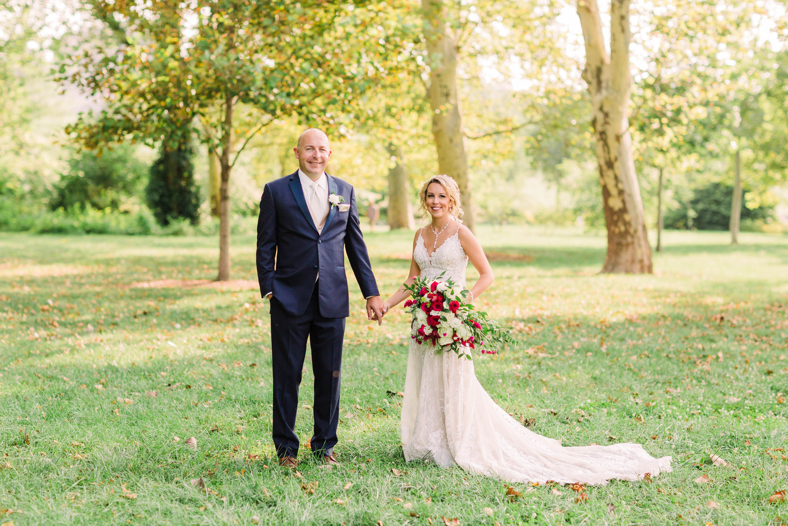 Bride and groom, Jenn and Danny, pose side by side in a lush green field near the Grand Basin in Forest Park