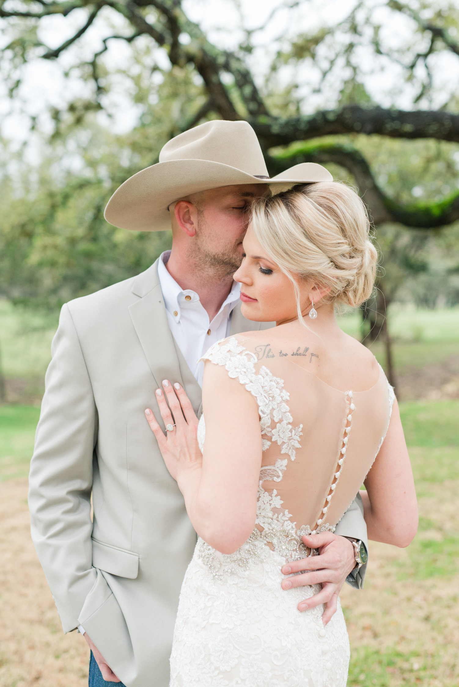 Groom kisses bride on the forehead at their Rustic Ranch Wedding in Wimberley, Texas