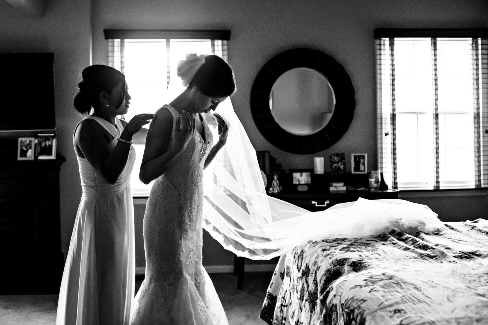 The maid of honor helps a bride put on her wedding dress in her childhood bedroom.