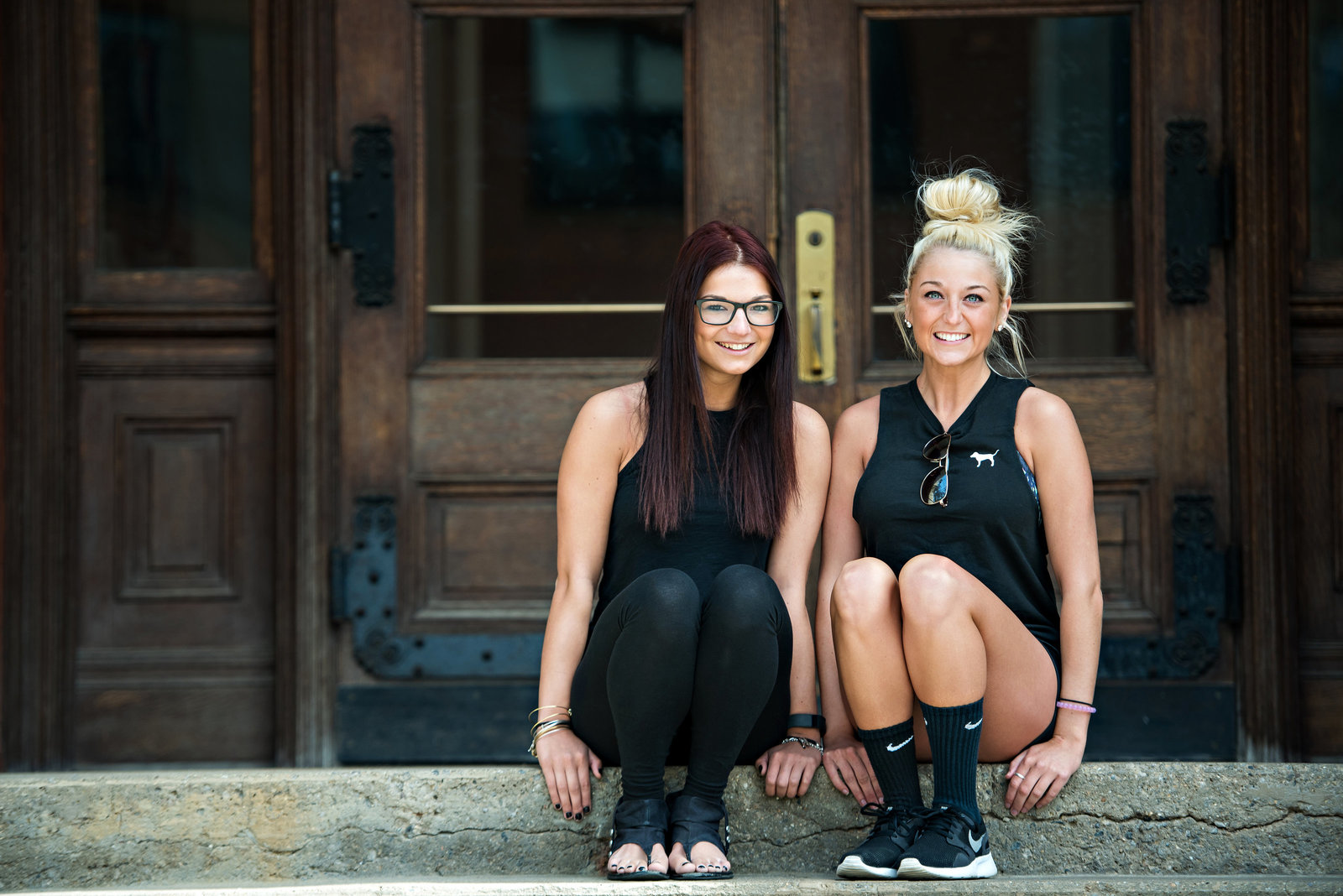 Two college fitness students sit on the steps on campus.