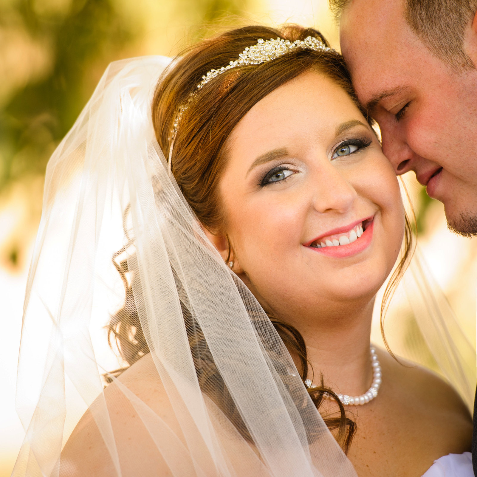 A bride smiles with her groom leaning on her after their wedding at Kickapoo Winery near Peoria, Illinois.