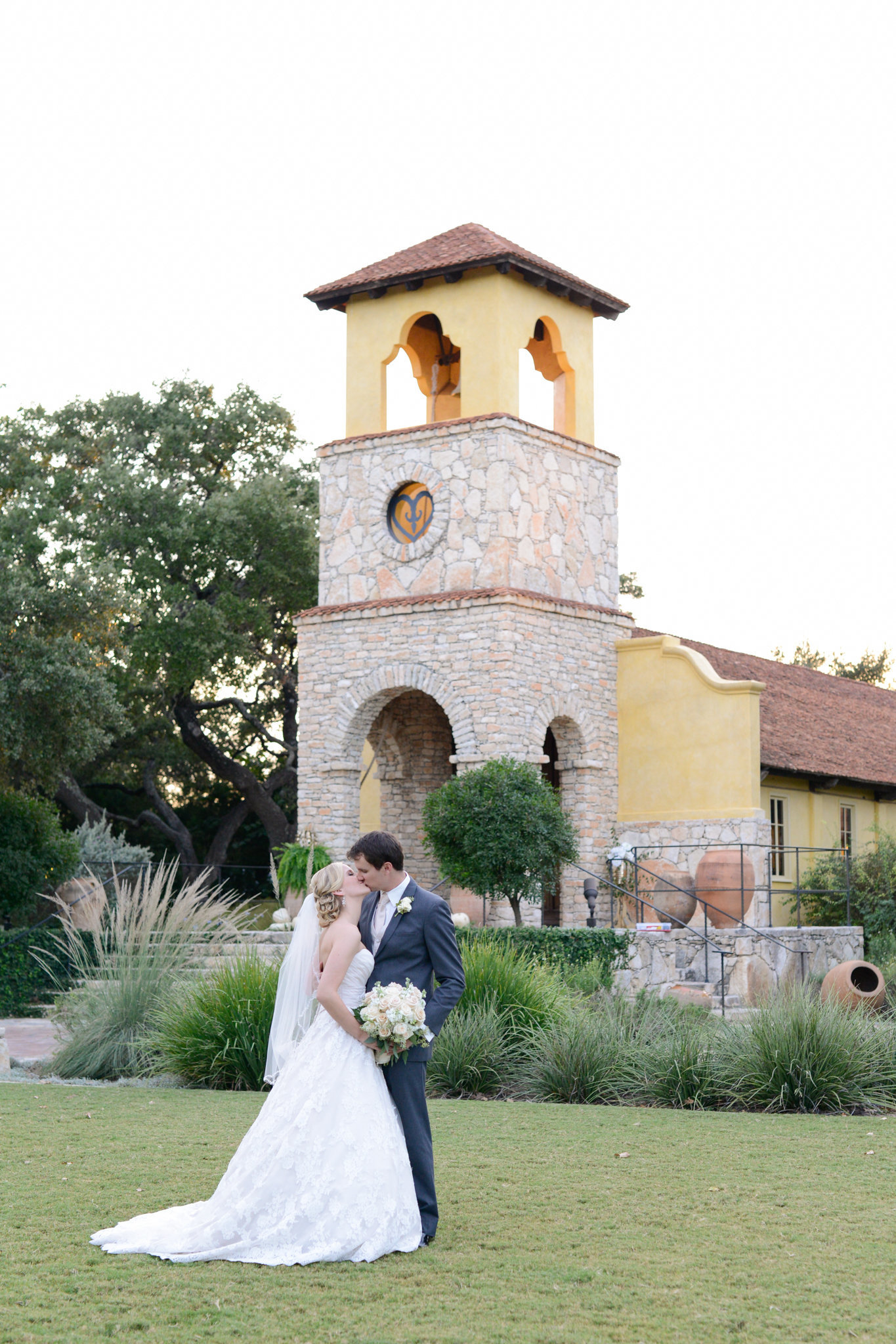 Groom kisses his bride at Ian's Chapel of Camp Lucy Wedding in Dripping Springs