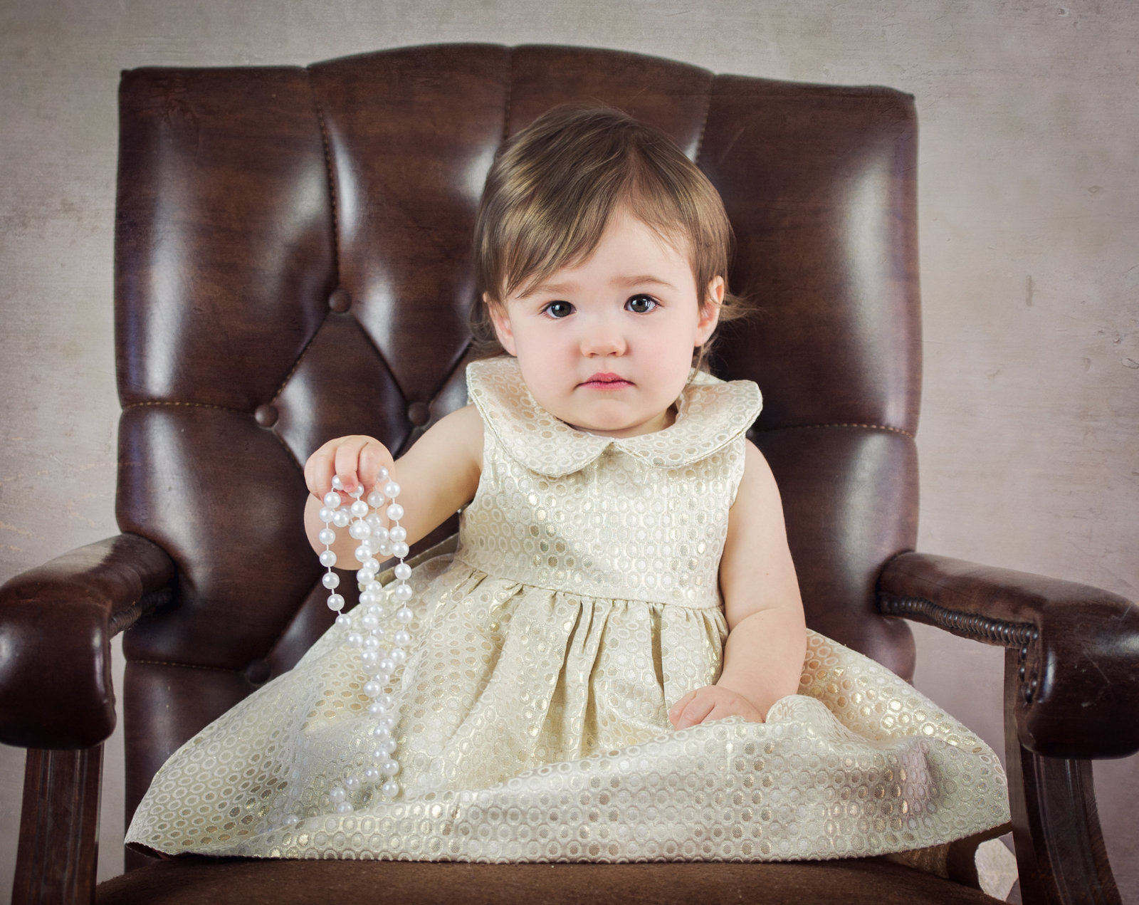 little girl in cream dress and pearls