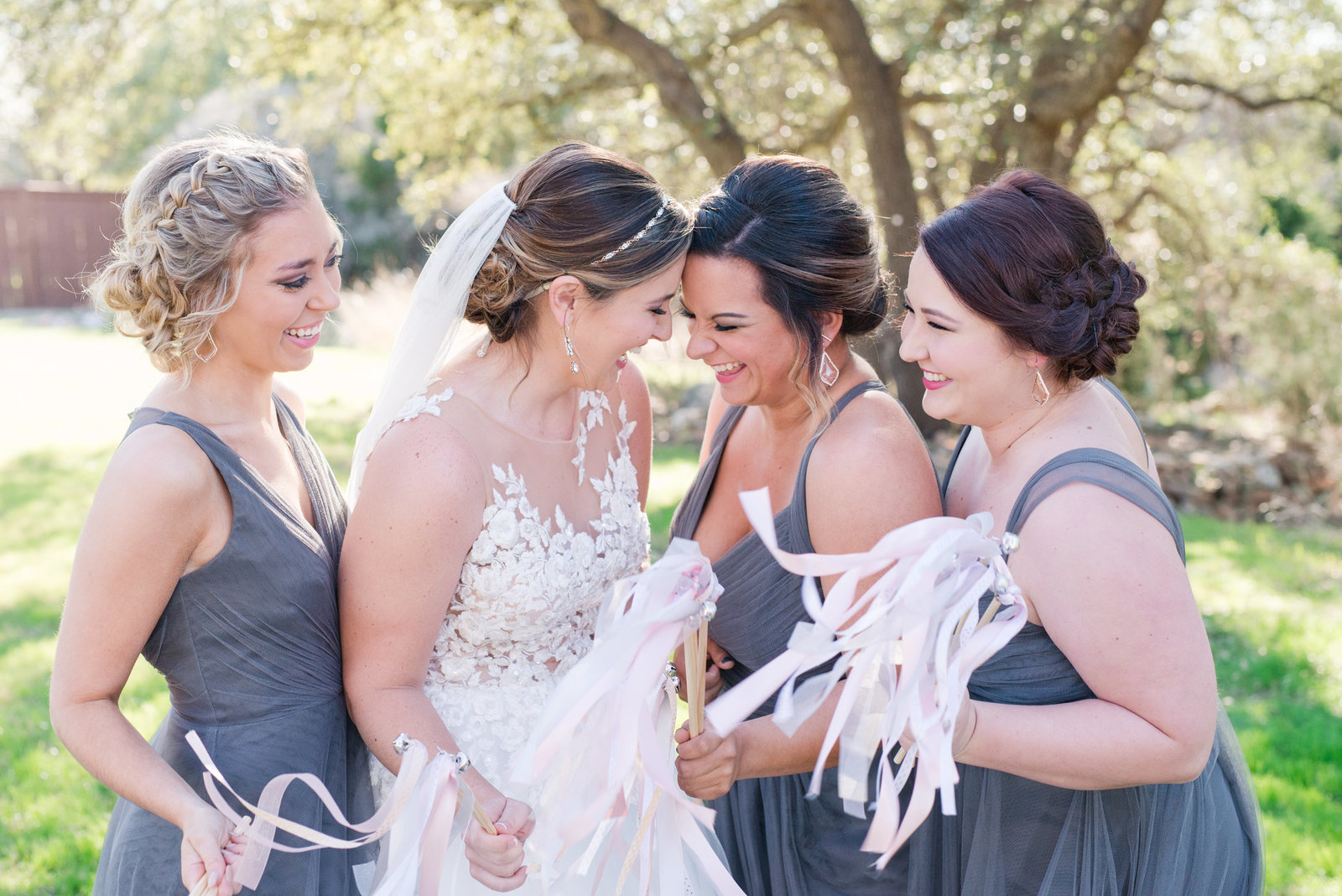 bridesmaids in gray laugh as the wave blush ribbon wands at Georgetown wedding