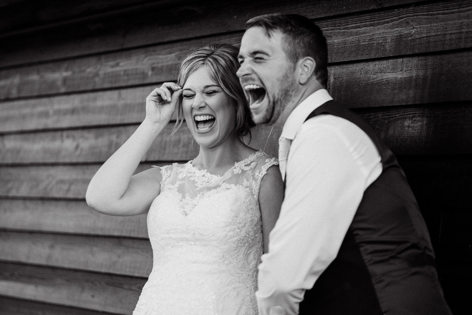 Bride and groom really being in the moment in hysterics against the fenced wooden panelled wall at Farbridge Wedding Barn in West Dean