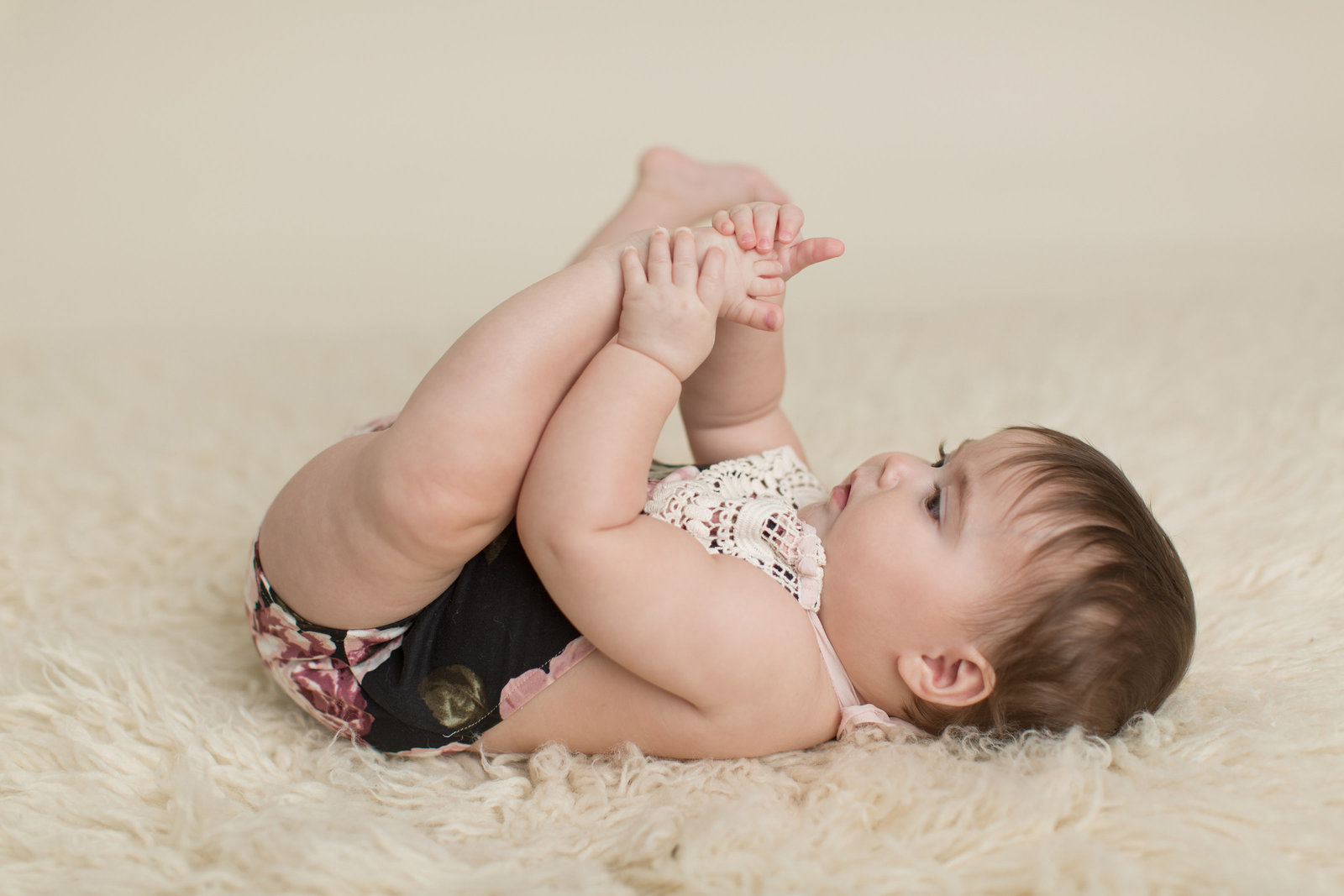 girl plays with little toes laying on fur backdrop