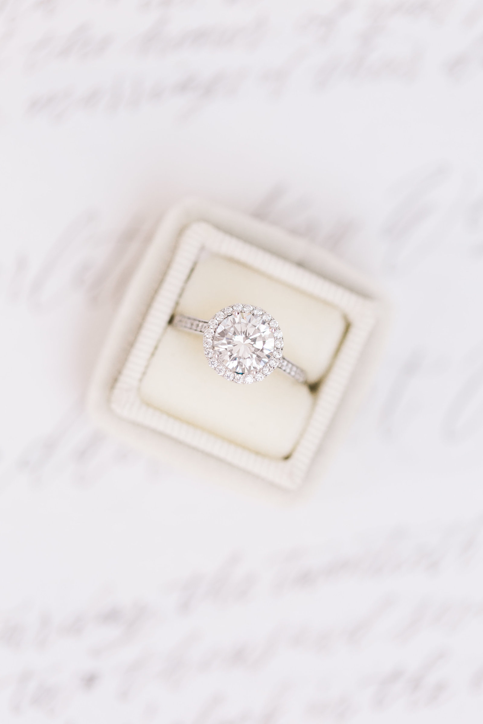 Encrusted diamond ring in box sitting on top of a wedding invitation