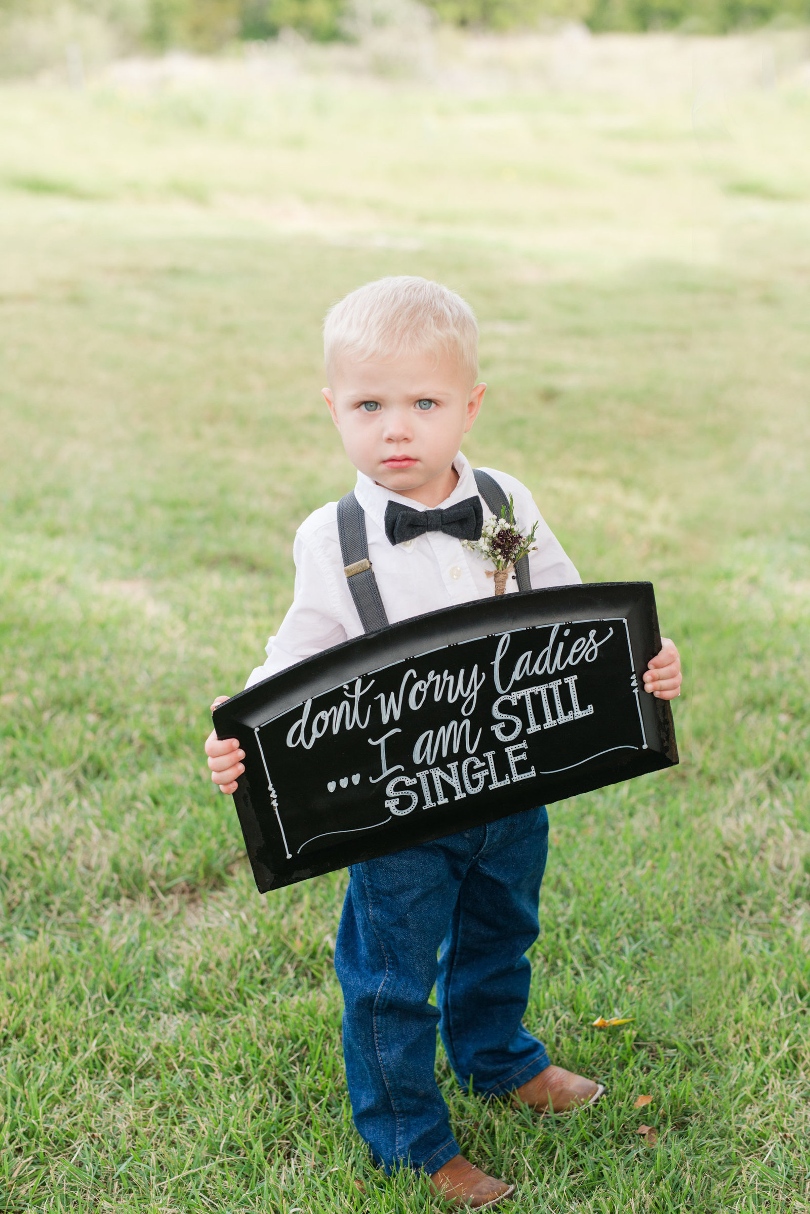 "Ring Bearer in boots and bow tie holds sign that says ""Don't Worry Ladies, I'm still single"""
