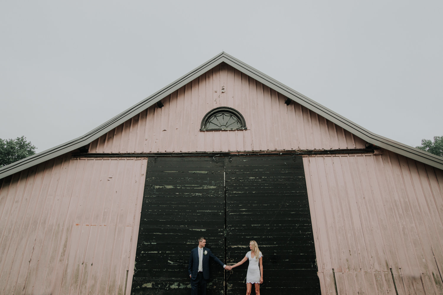 pink barn with the bride and groom
