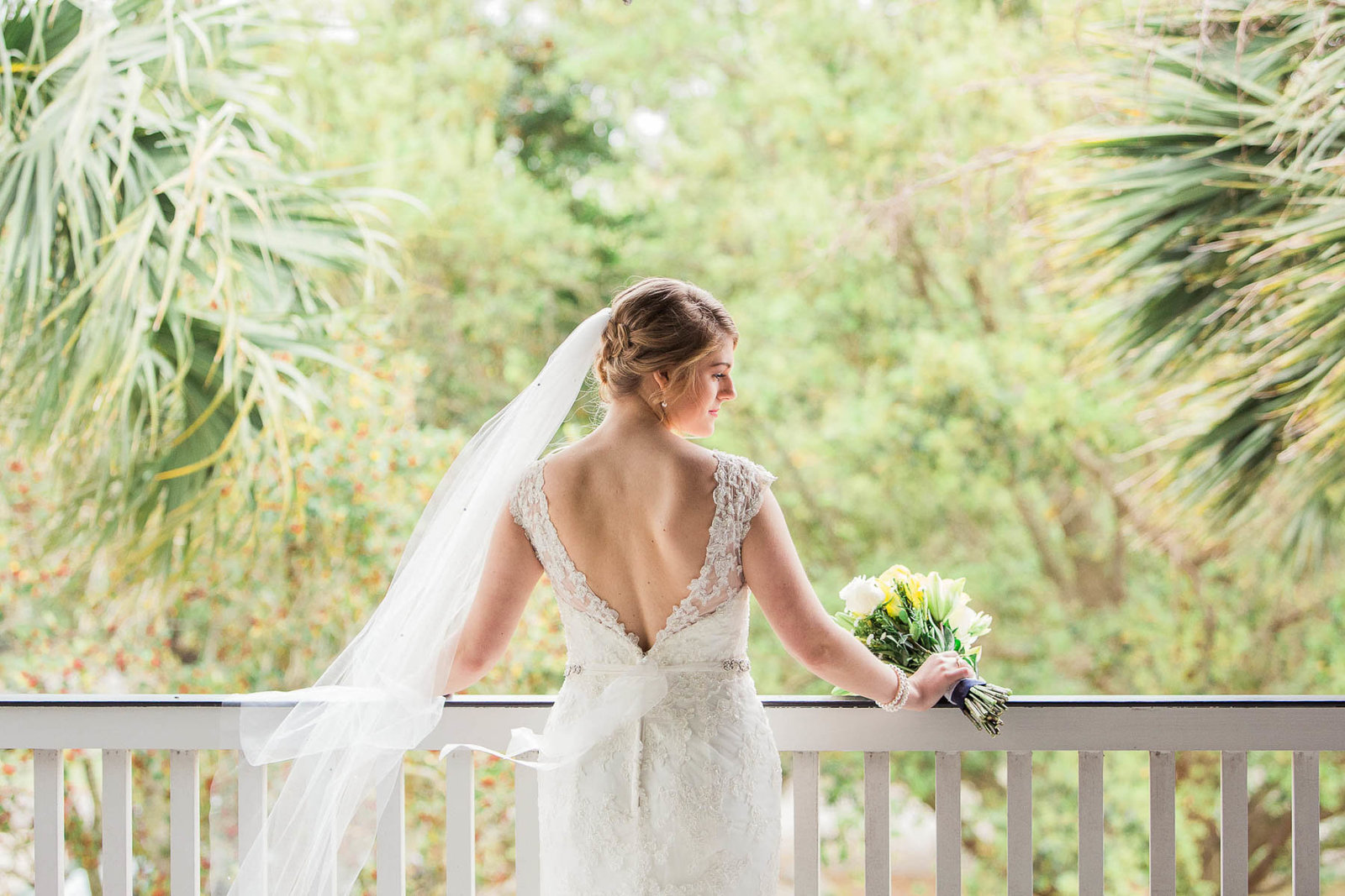 Bride leans on railing with veil blowing, Alhambra Hall, Charleston, South Carolina