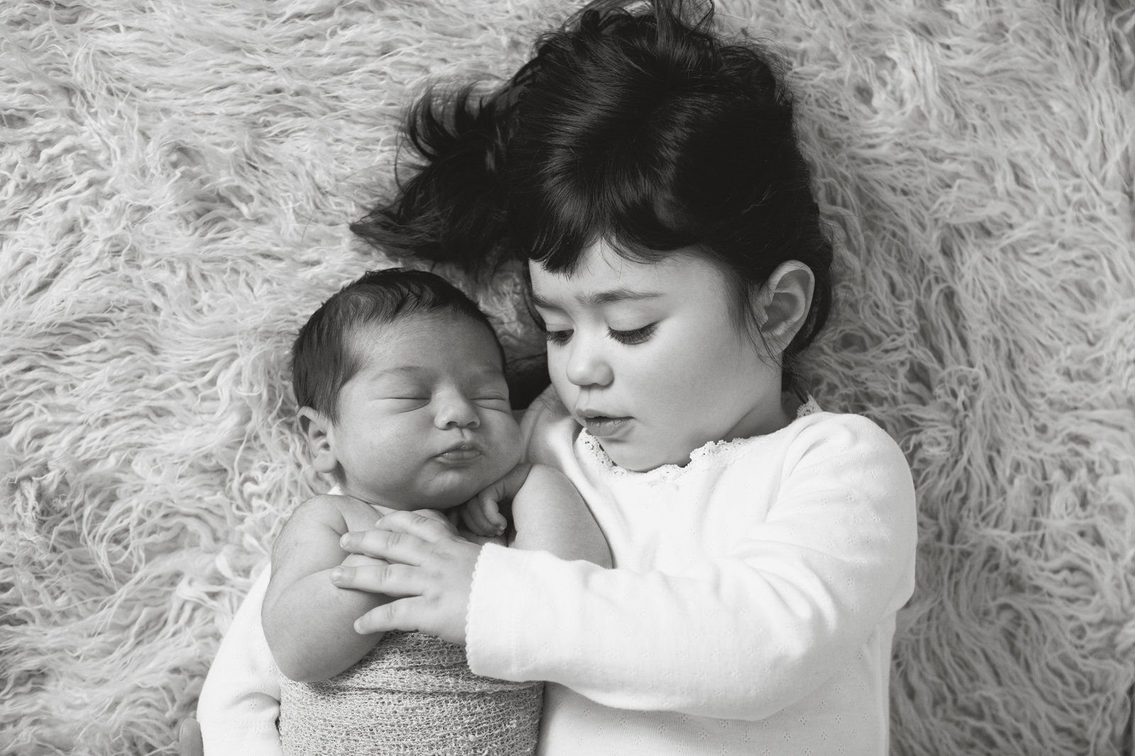 Big sister snuggling with newborn baby sister photos by Hudson Valley professional photographer in Cornwall NY photography studio