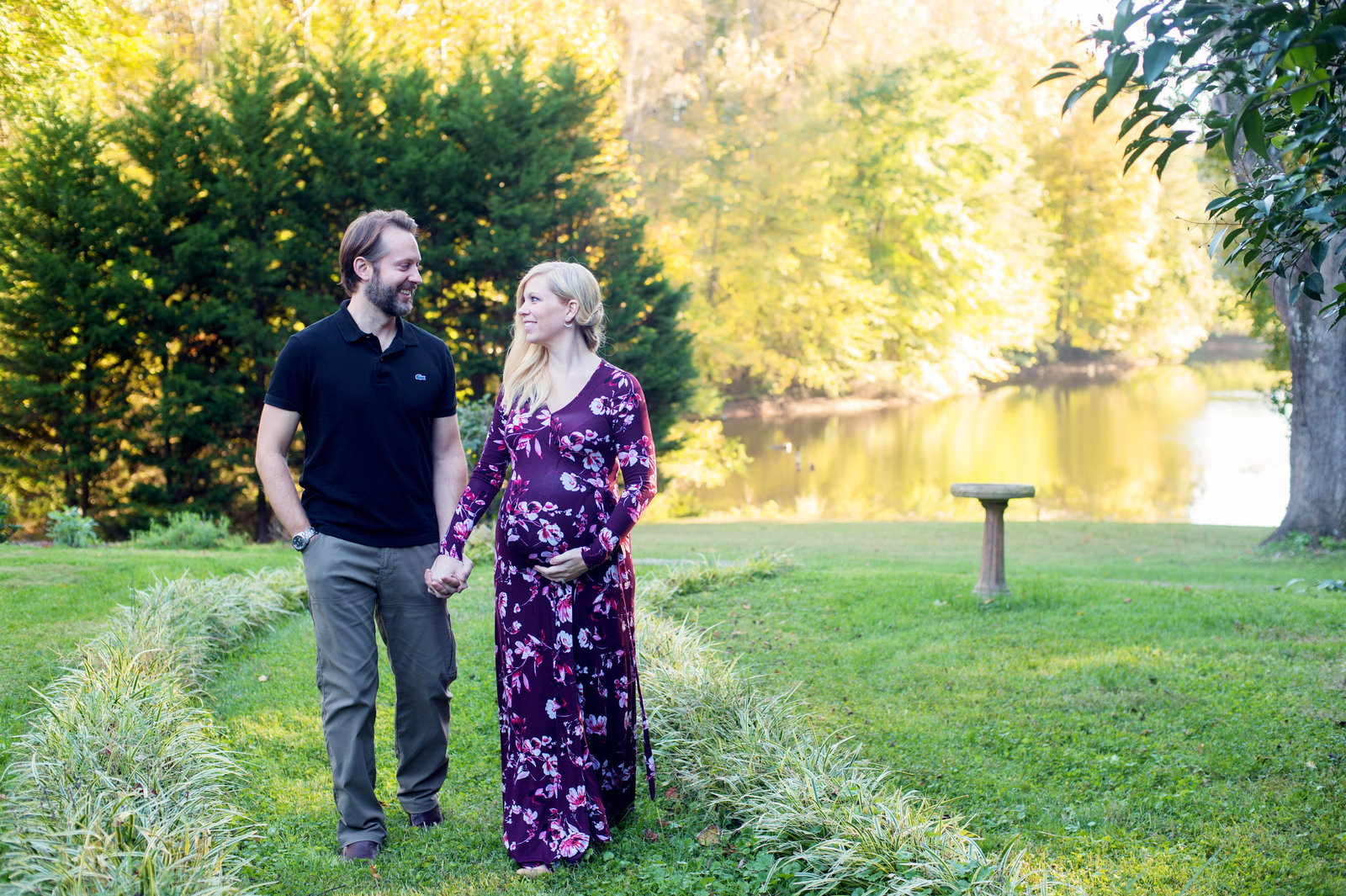 a husband and pregnant  wife walk hand in hand in front of a lake in their backyard