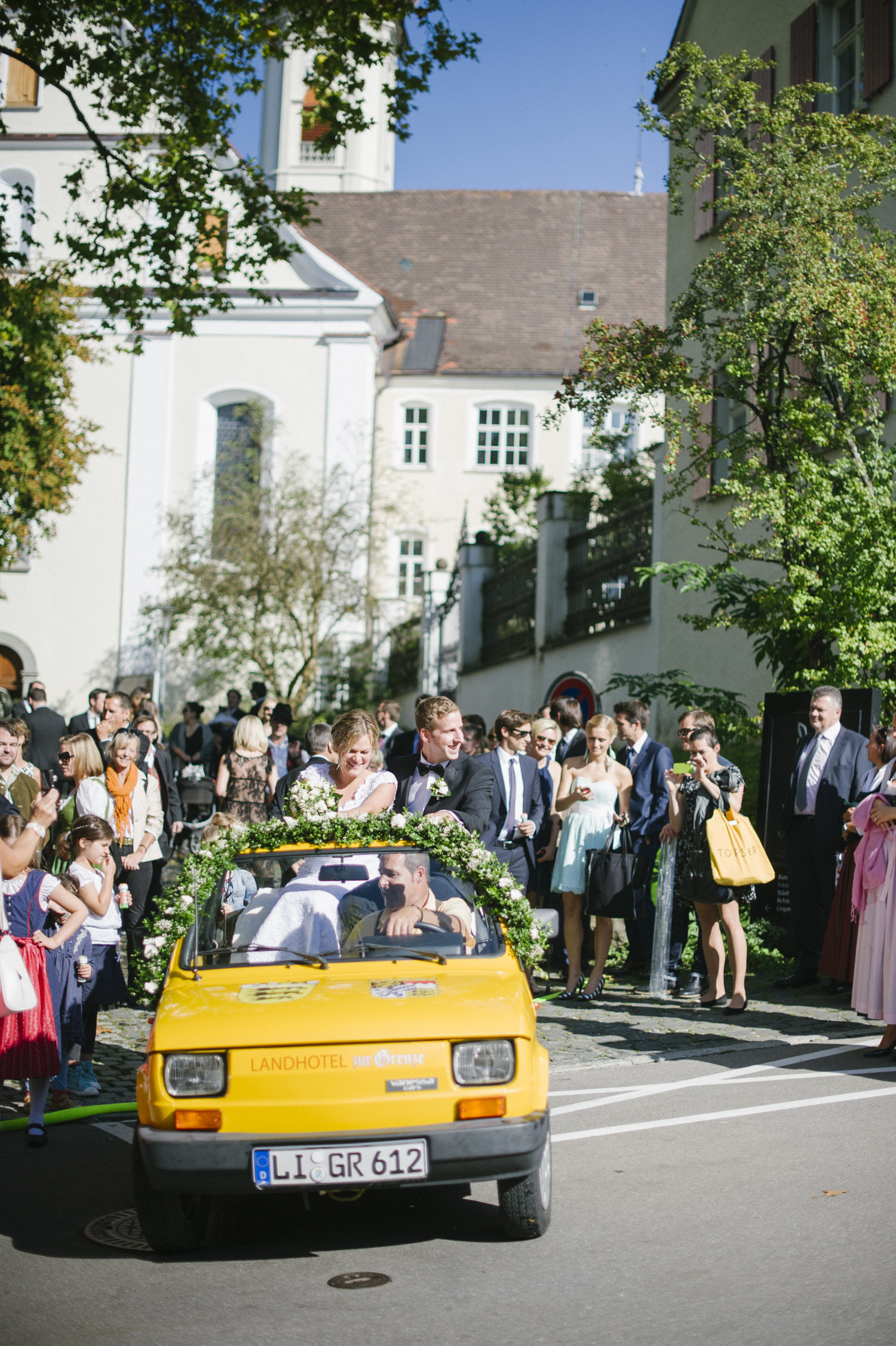 bride and groom greeting wedding guests isny town bavaria after church ceremony