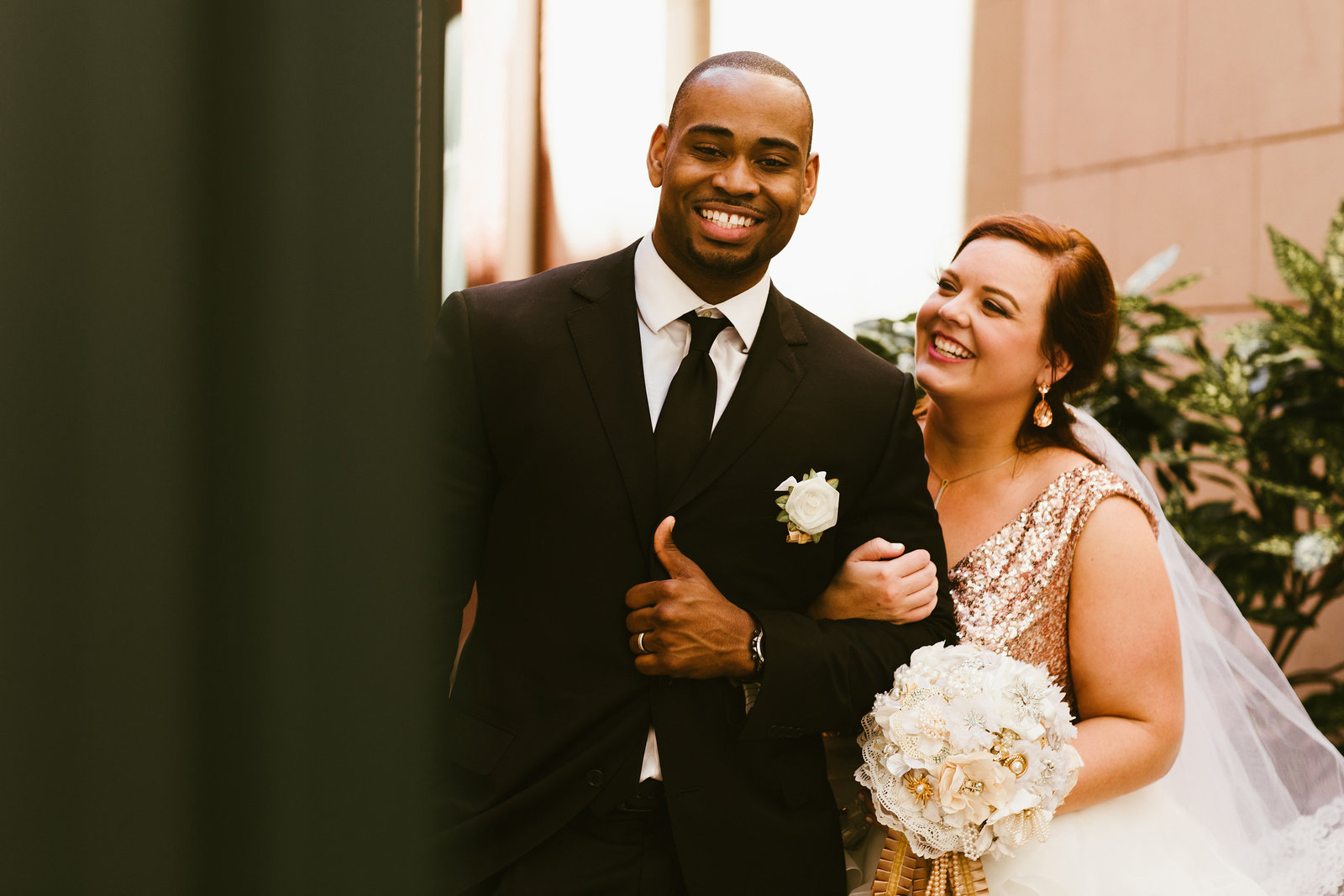 groom in black tuxedo and bride in pink sequined wedding gown smiling together at their Memphis wedding