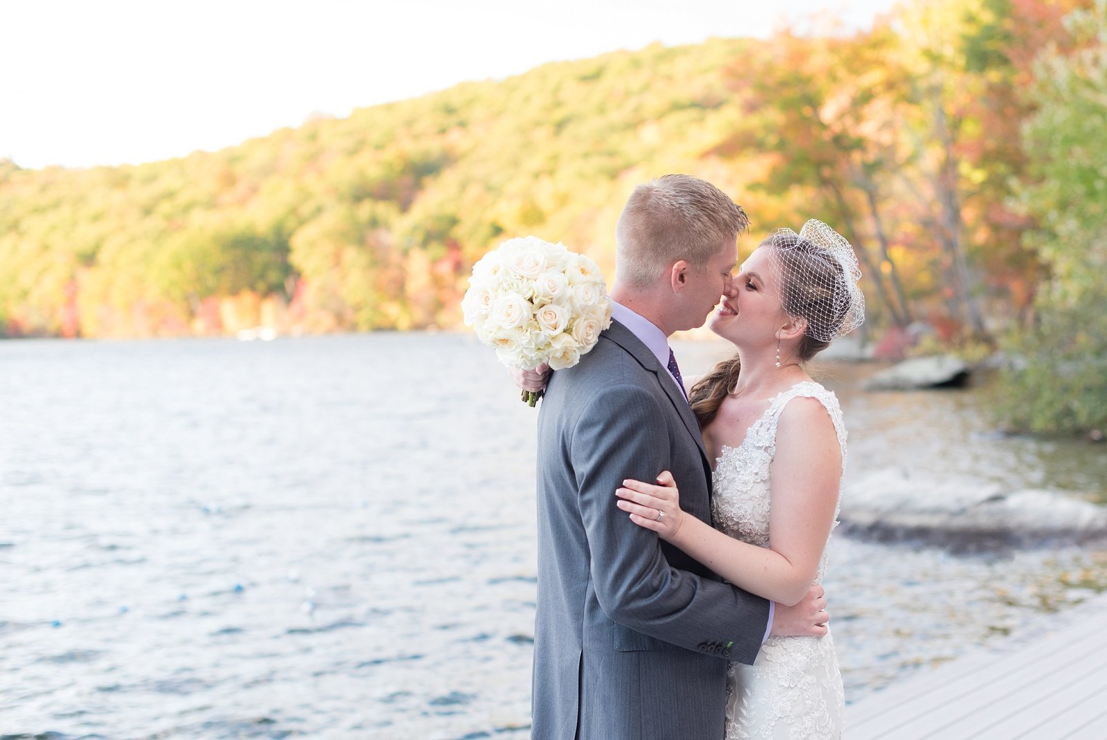 Bride and Groom snuggle together along the water with changing fall leaves at Sedgewood Country Club in Carmel, New York Photo
