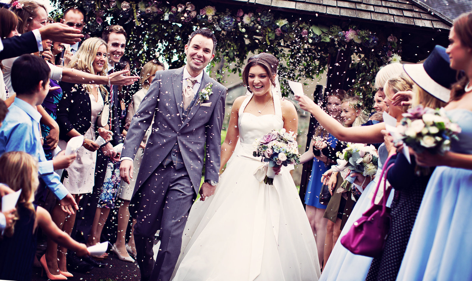 Bride and groom celebrate leaving St.Marys Church at The Inn at Whitewell in Lancashire