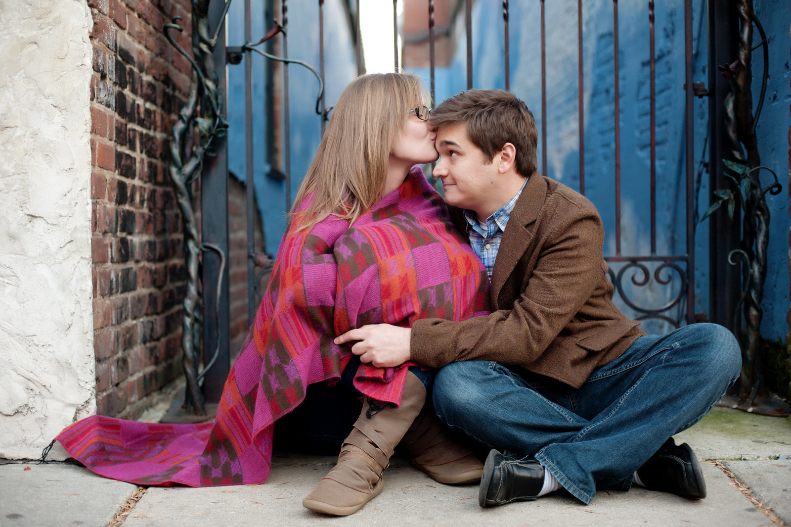 a girl wrapped in a blanket kisses her fiance's forehead sitting on the sidewalk