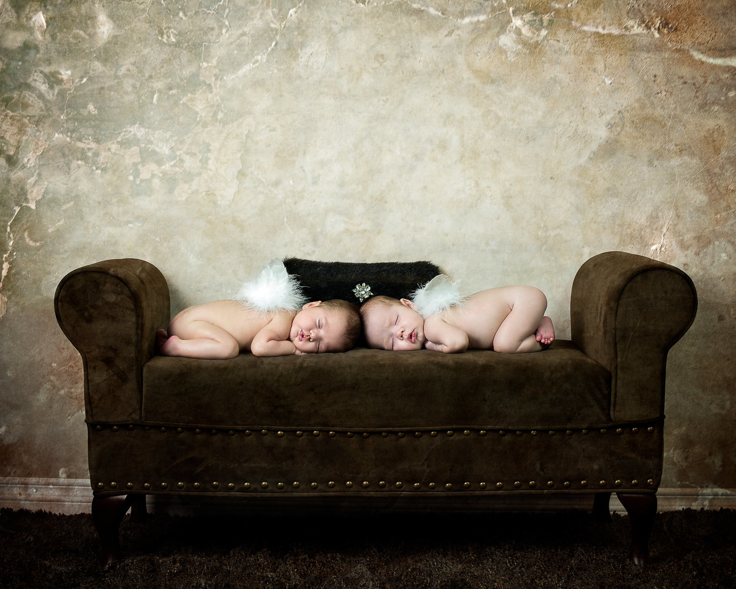 newborn twins with angel wings sleeping on couch with textured background