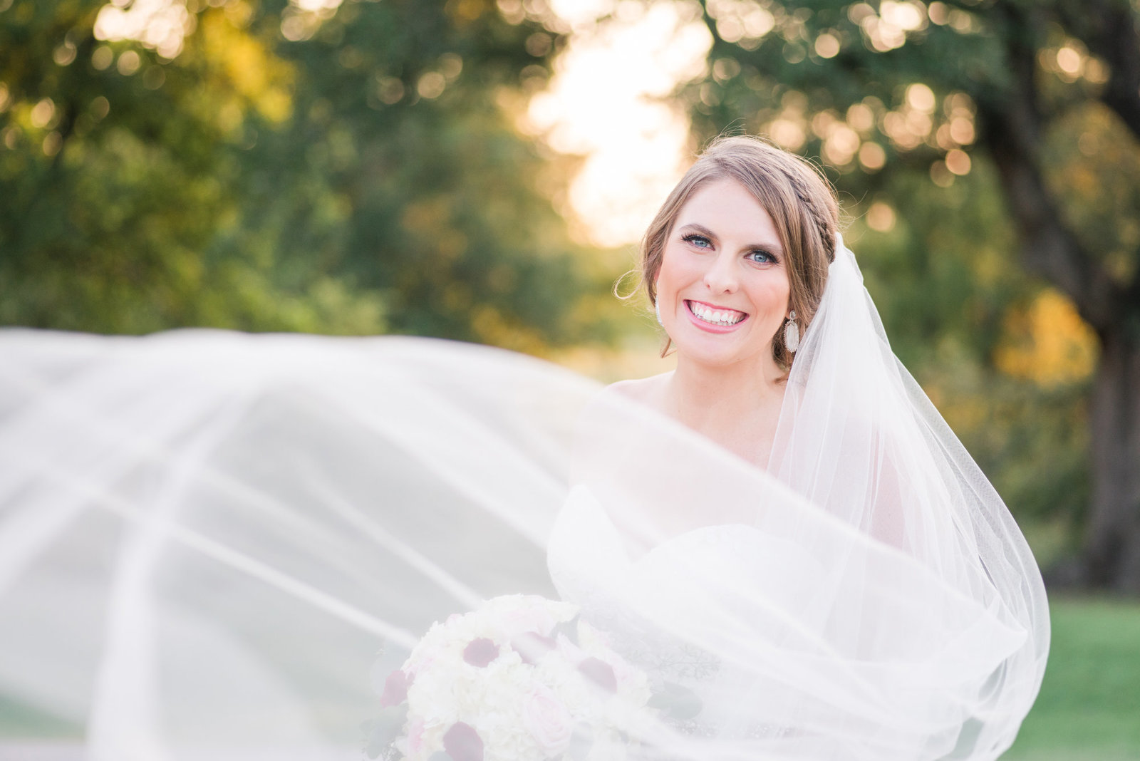 Bride's veil flies at the camera during her bridal session at Lone Oak Barn in Round Rock