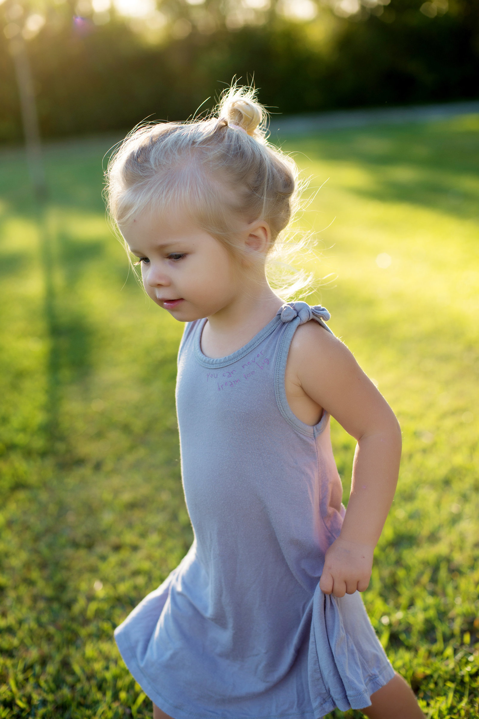 a blonde haired girl walks through the grass holding her dress