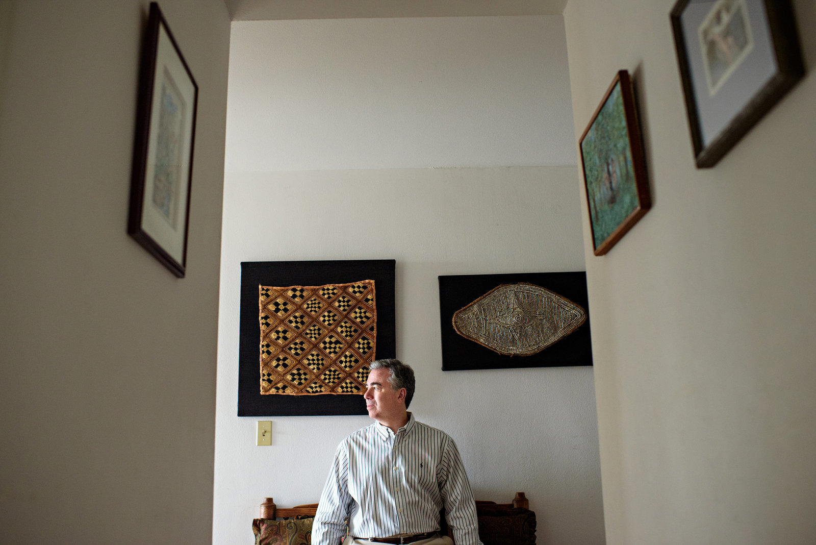 A man sits on a bench in the hallway of his home for this environmental head shot.