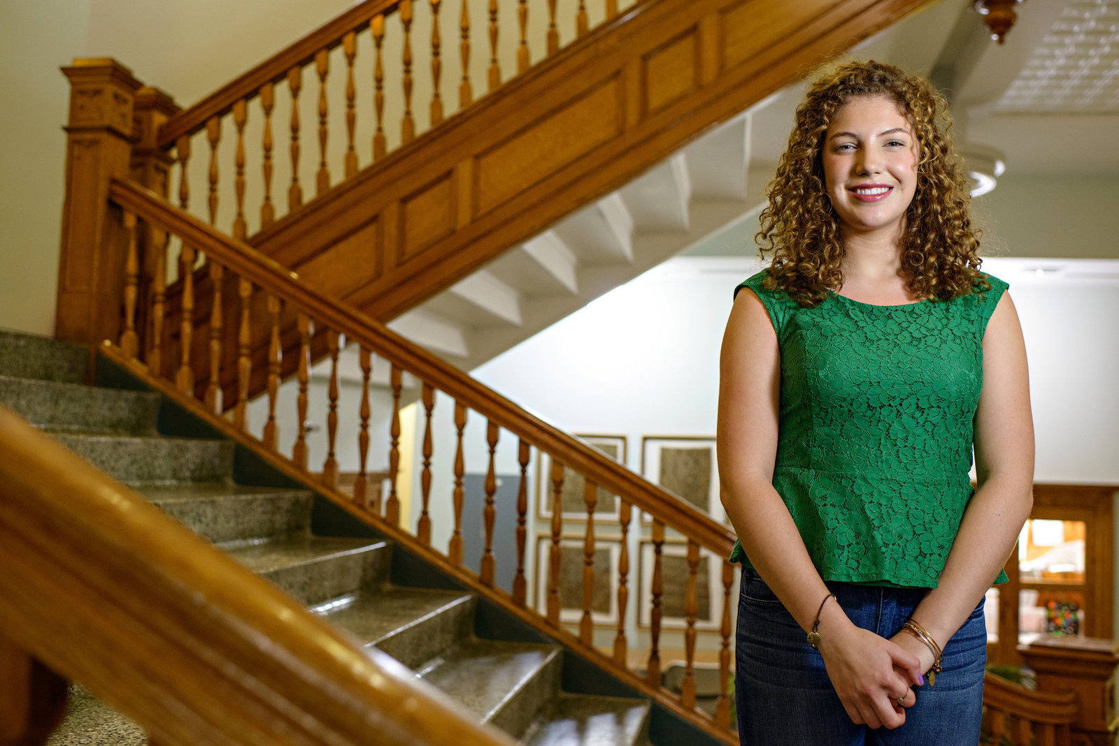A young professional woman stands in stairs and smiles.