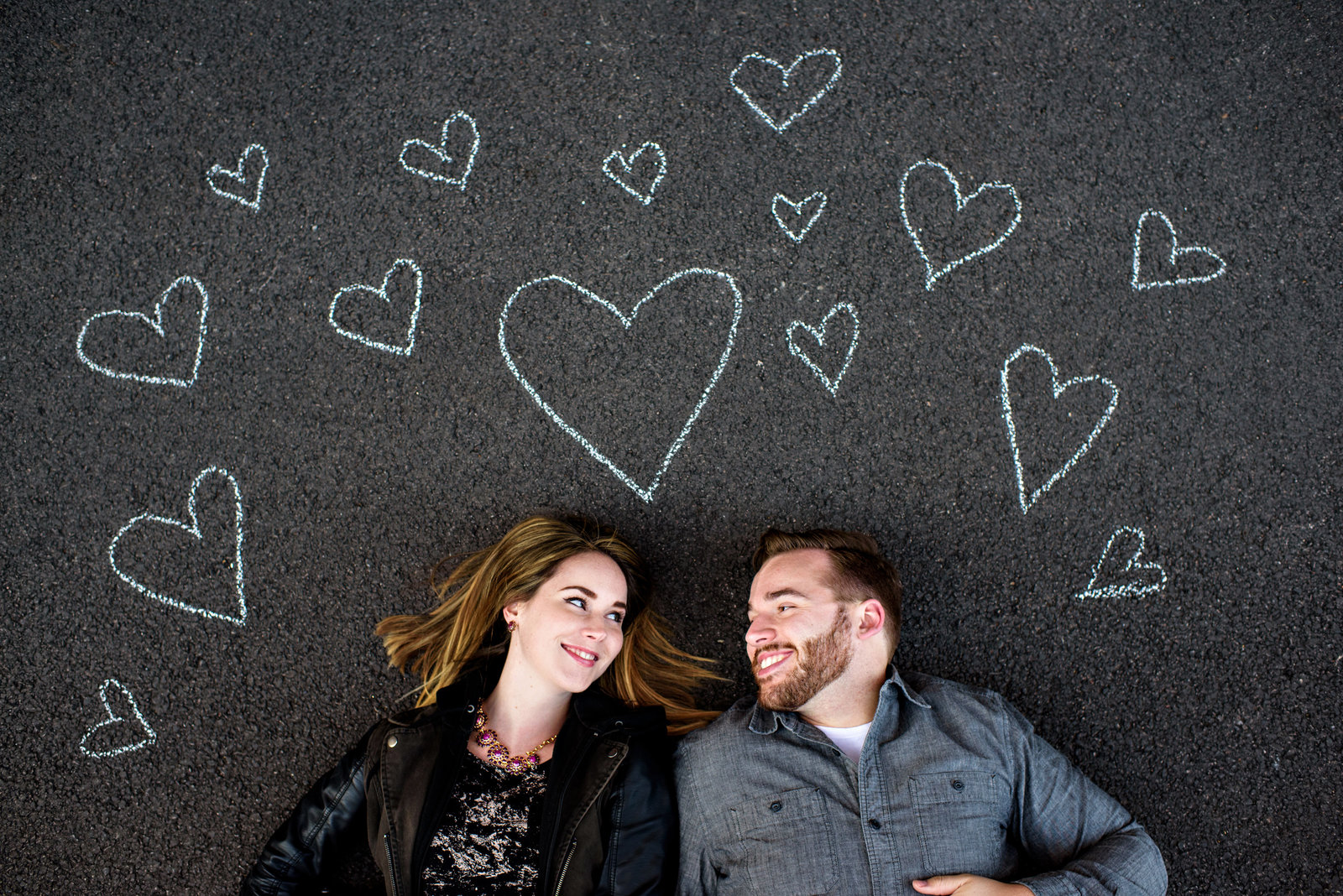 A loving couple lay on the ground surrounded by chalk hearts drawn around them.