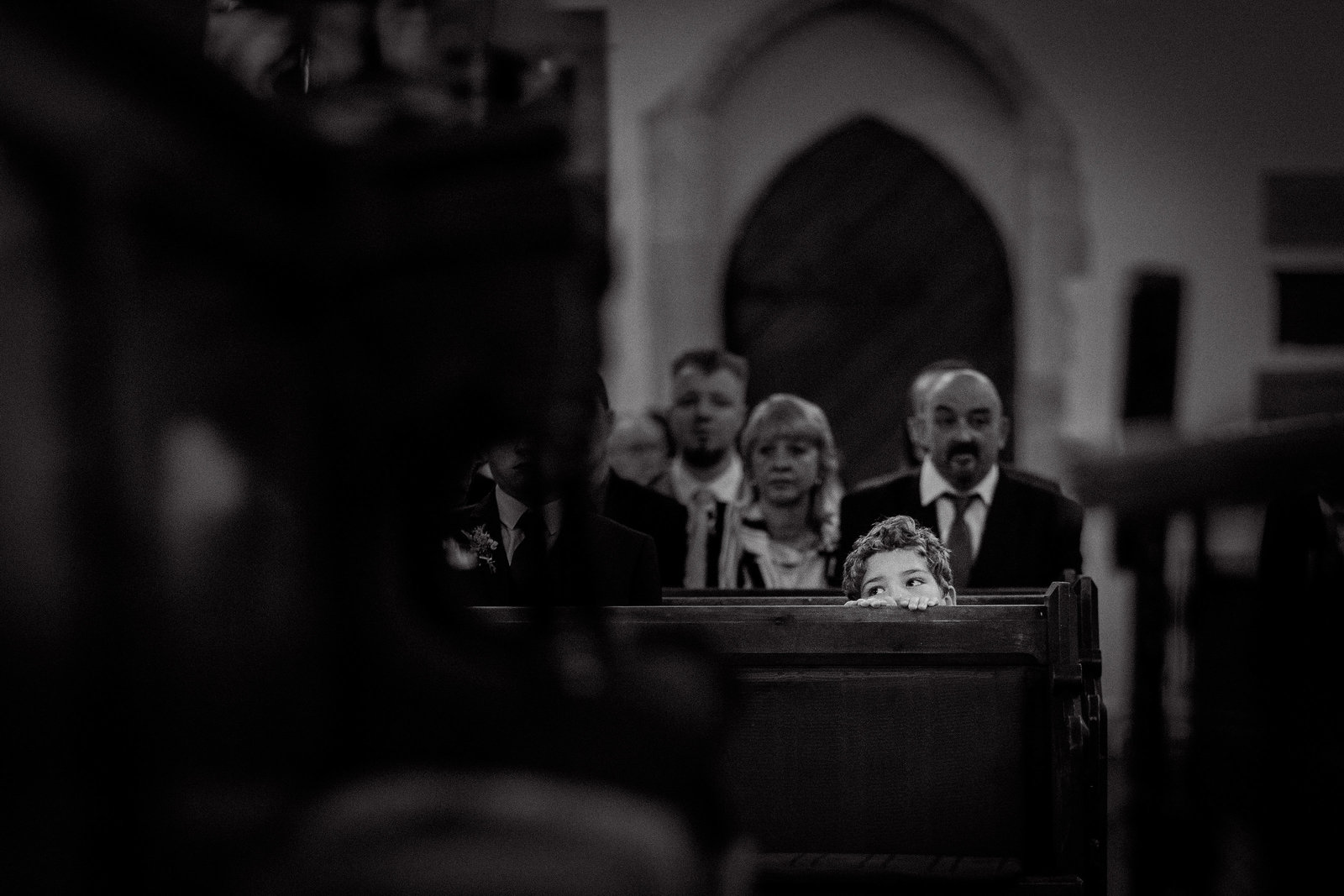 Page peeks over the pew in the church in this beautifully captured black and white documentary photograph captured by Adorlee in natural light