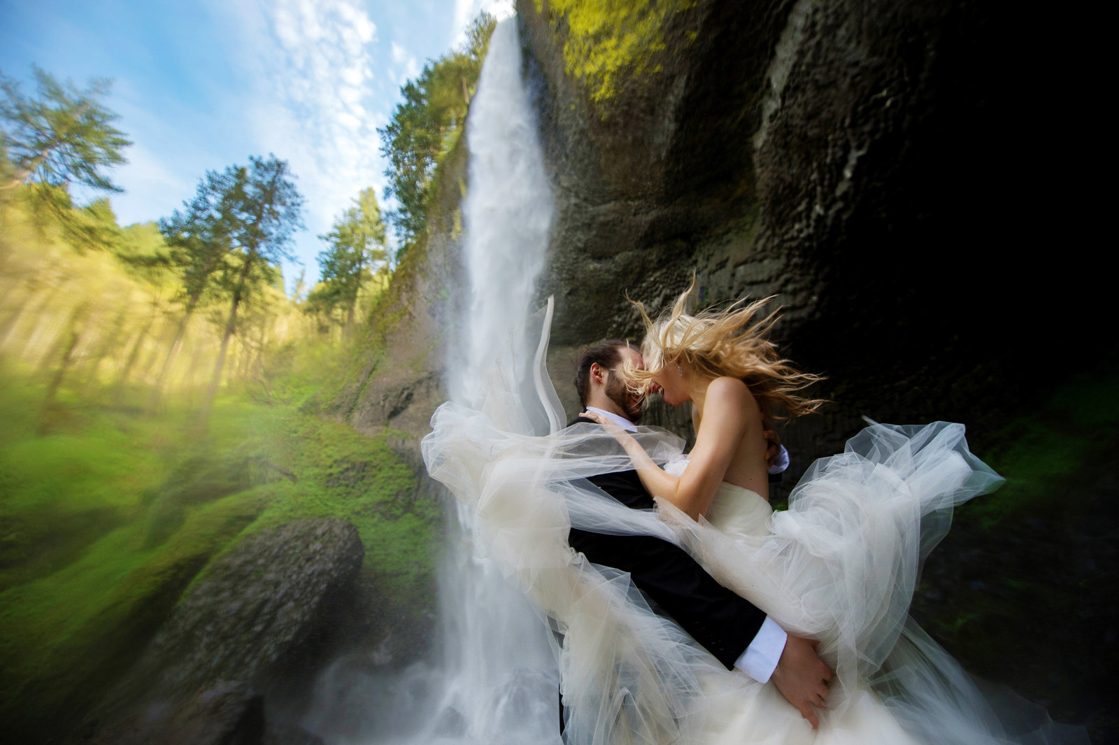 a couple stands under latourell falls on a windy day after their wedding