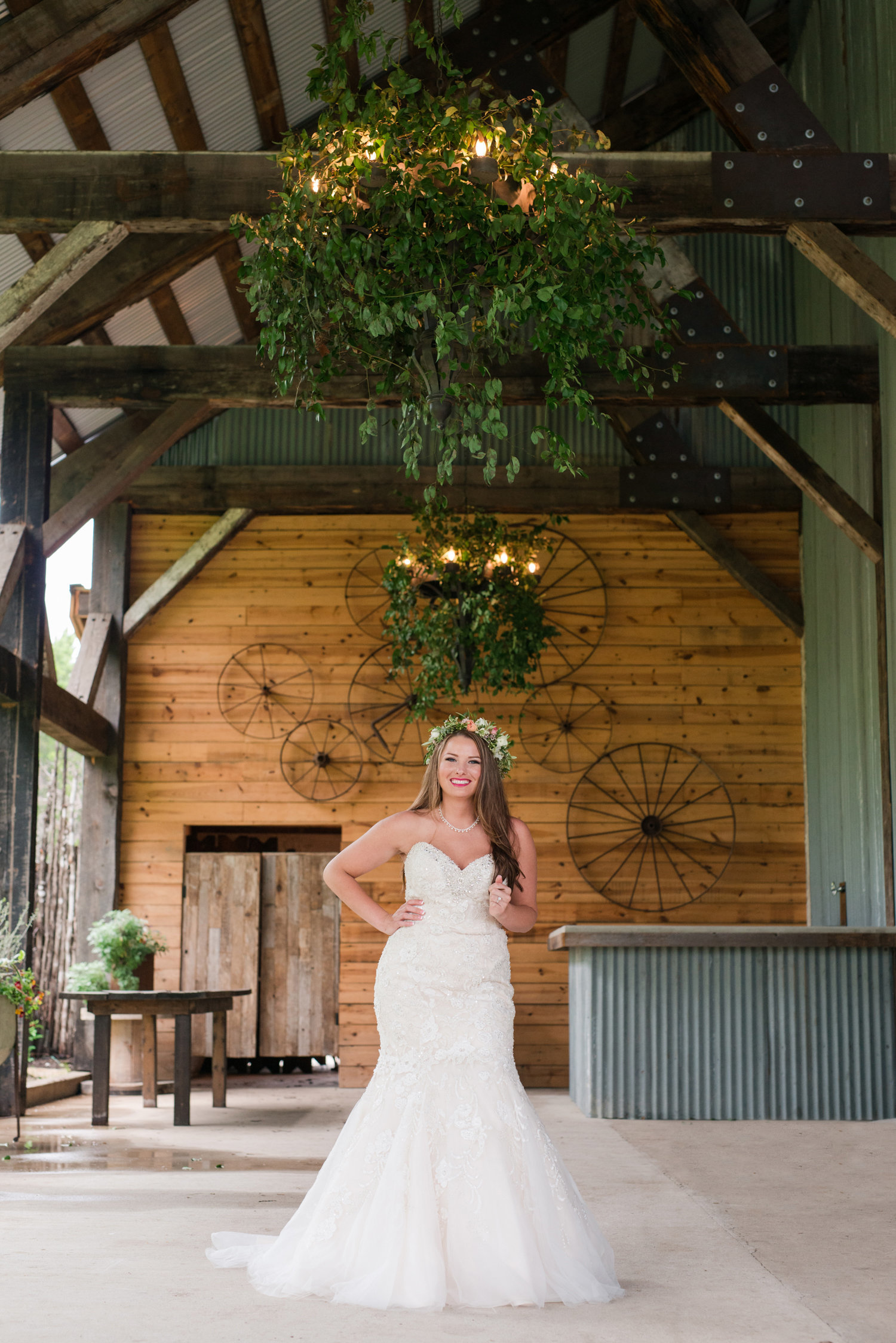Bride laughs in pink flower crown with wagon wheels behind her at The Creek Haus in Dripping Springs, TX