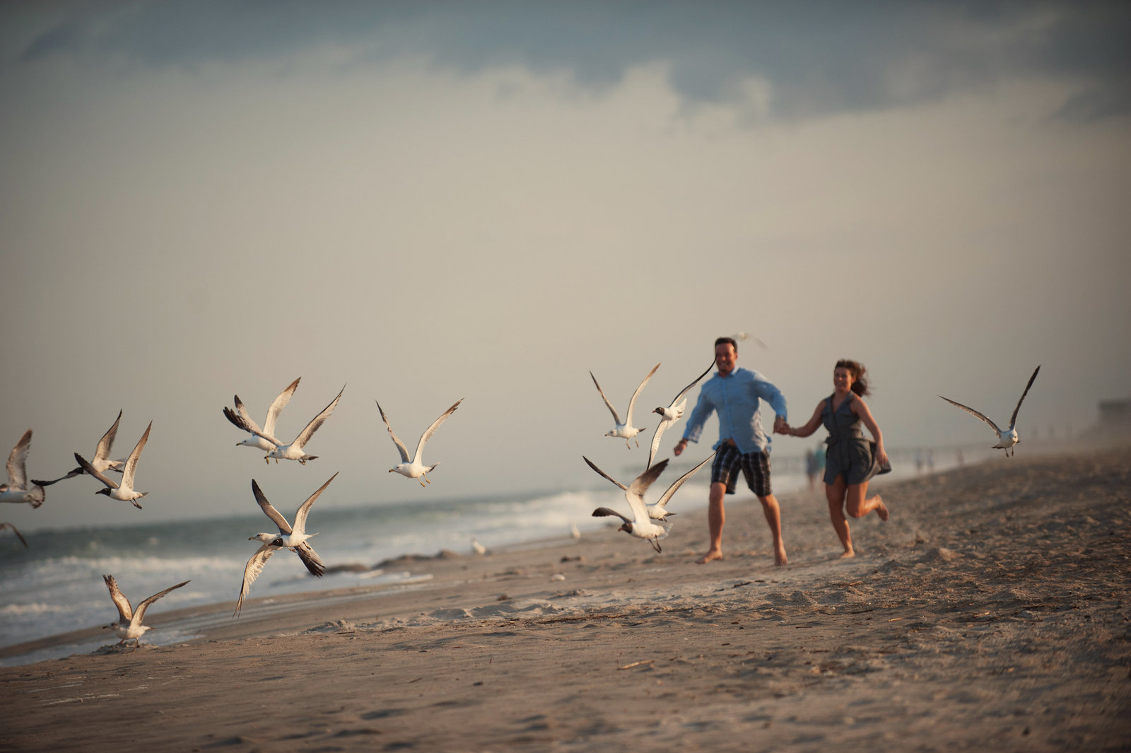 a couple run through a flock of seagulls at wrightsville beach