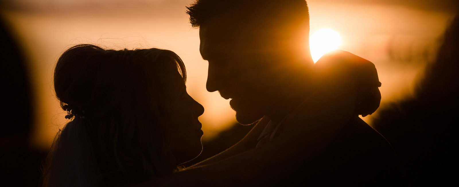 Taken by Adorlee at Golden Hour, this bride and groom have the perfect loving silhoutte embraced for the wedding portraits at sunset
