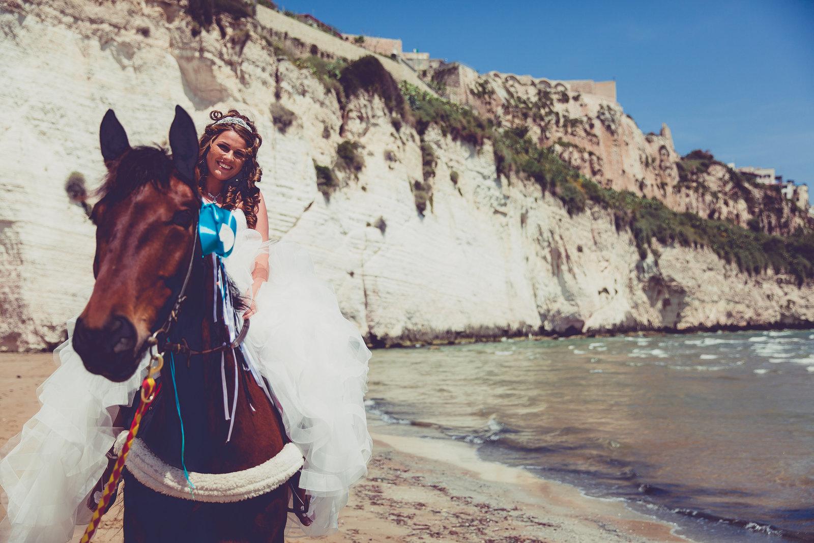 Geen rpins op het witte paard, maar een bruid op een bruin paard op een Italiaans strand. Copyright Nanda Zee-Fritse | FOTOZEE