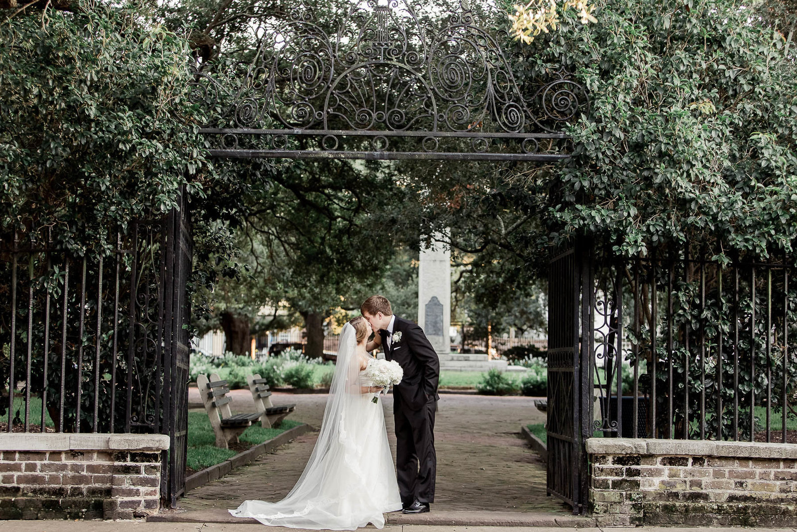 Bride and groom stand at the wrought iron gate of Washington Square, Charleston, South Carolina