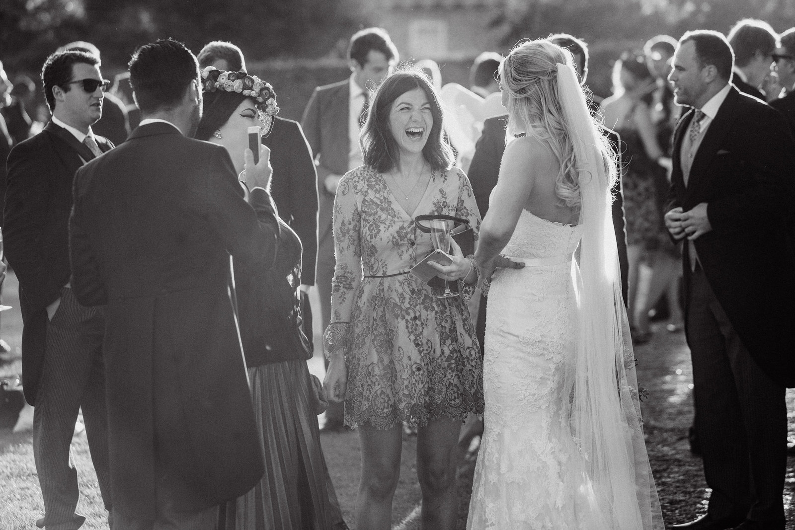 Natural light black and white wedding photo of the bride chatting to her guests at Goodwood House with sun flare, taken in a true documentary style by Adorlee