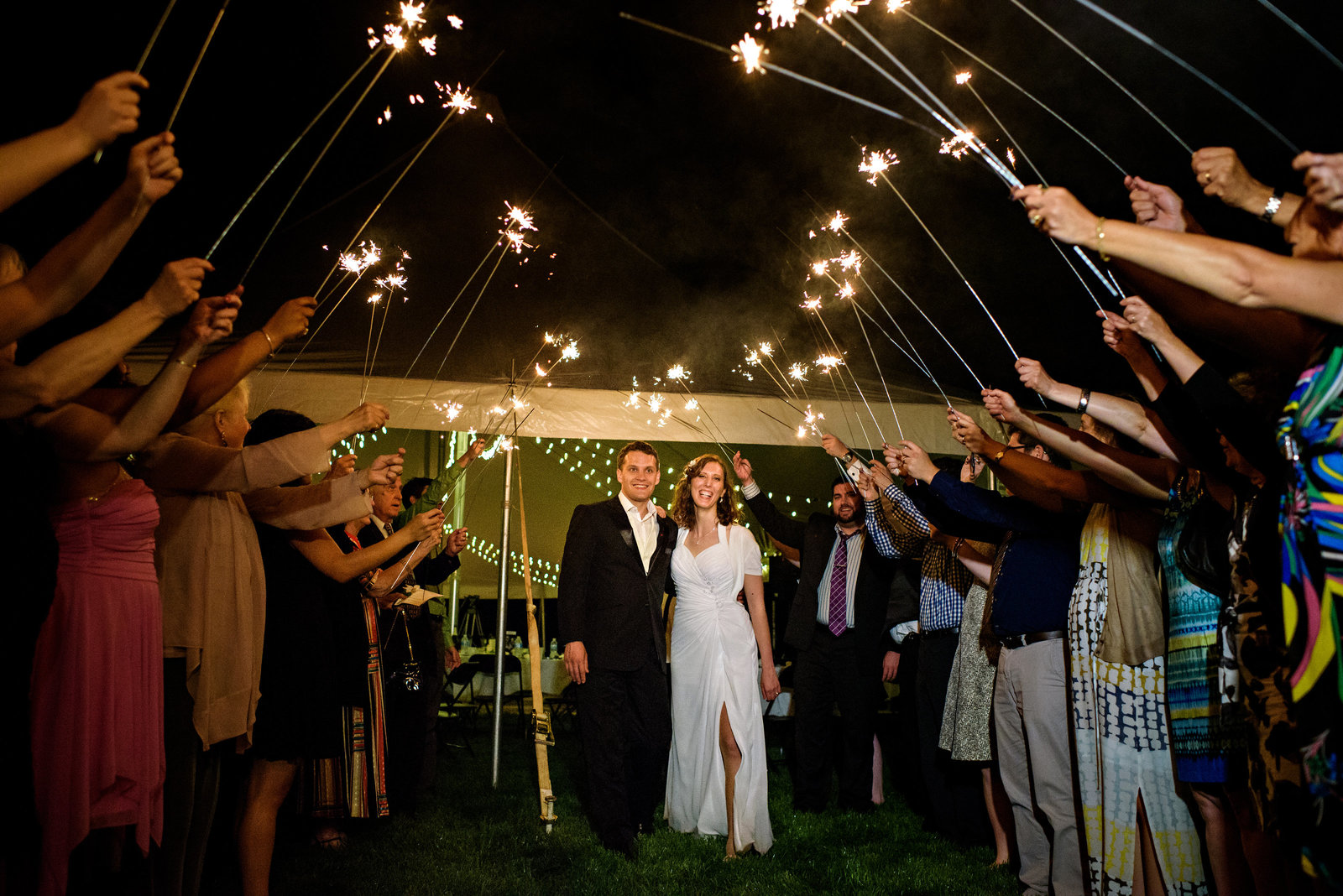 Wedding guests hold sparklers over a bride and groom as they leave the reception in bucks county PA.