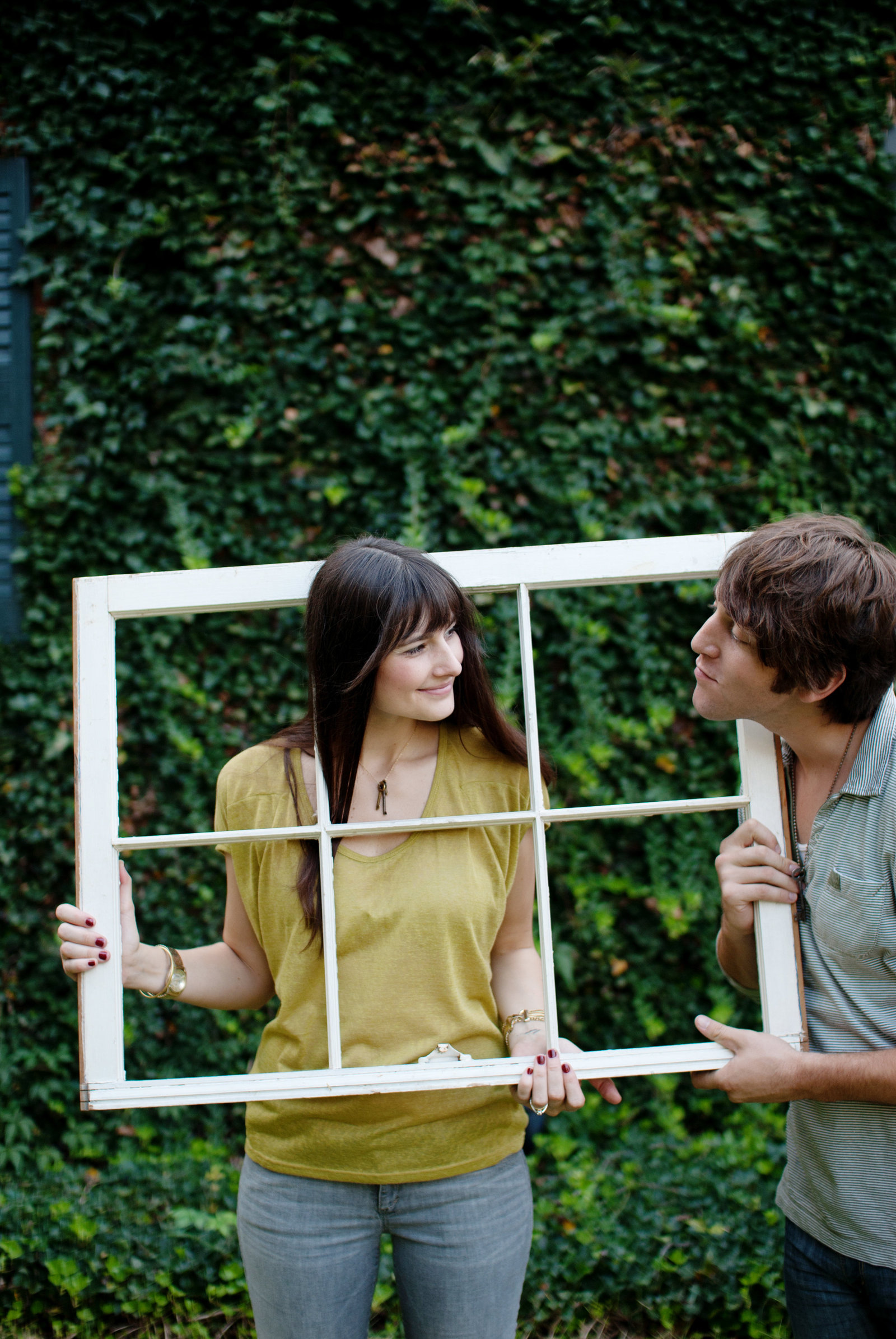 a girl holds a window frame and sticks her head through it to smile at her fiance