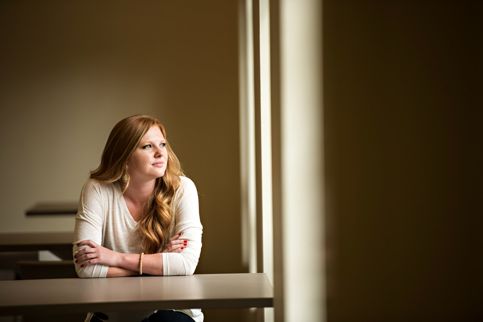 A red head sits at a desk in front of a window.