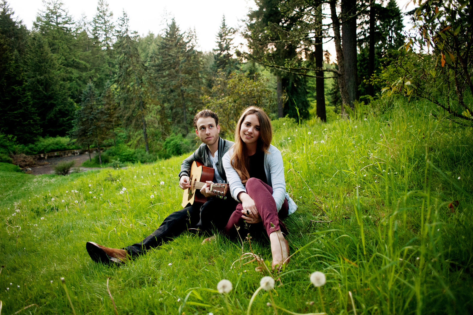 a couple sit in the grass at hoyt arboretum as her fiance plays guitar