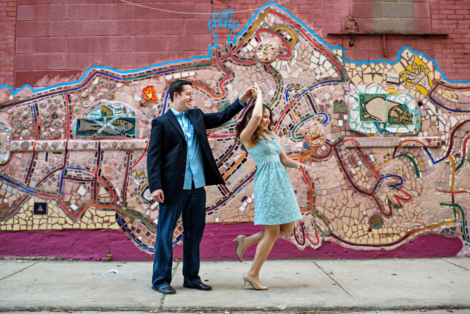 A newly engaged couple dance in front of a south philly mural.