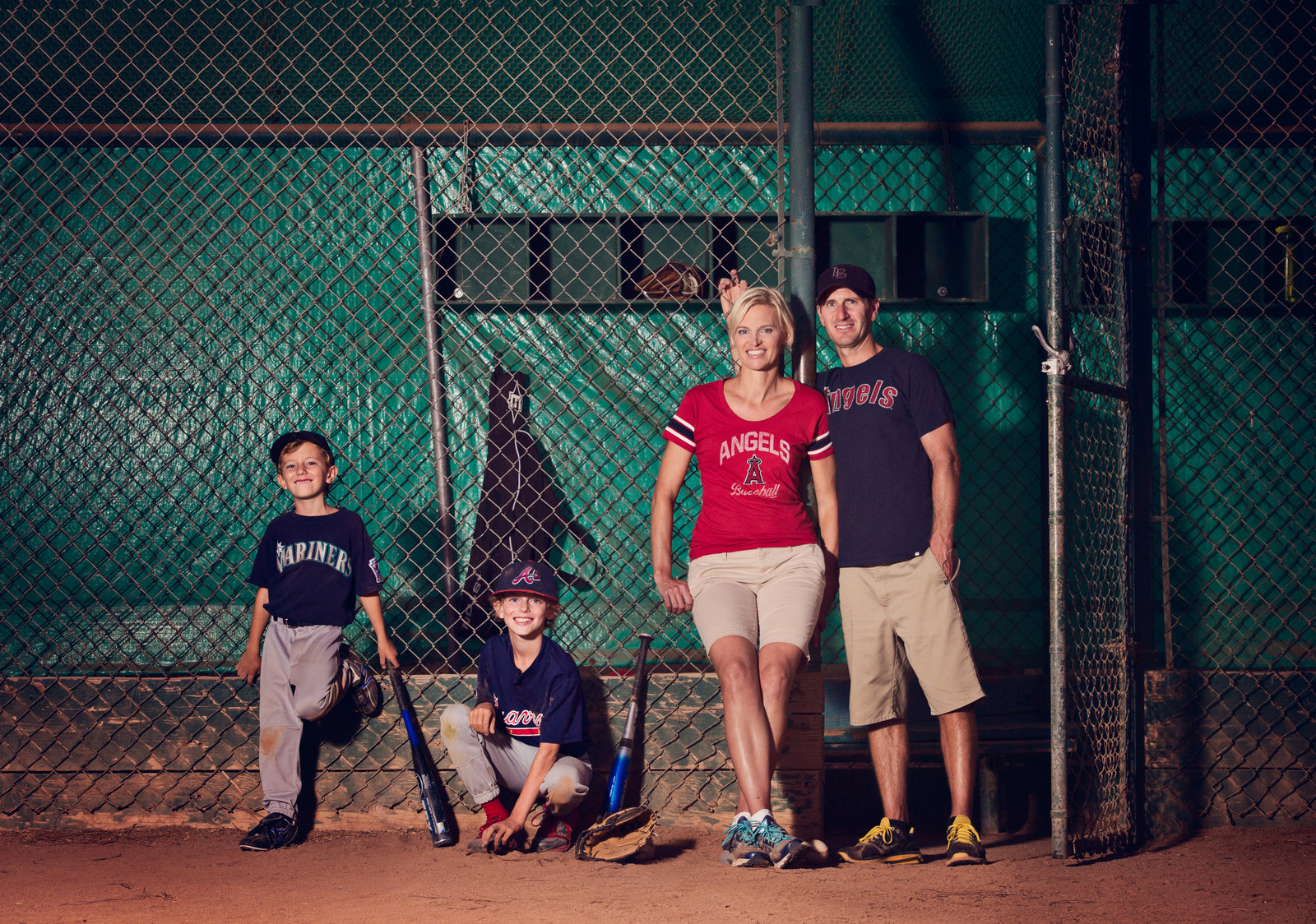Baseball themed photography session with family in baseball gear with baseball bats