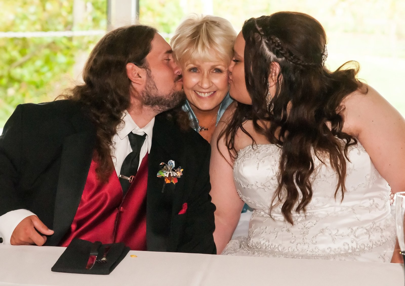 Bride and Groom give her mom a big kiss during their reception at White Oaks Winery near Peoria, Illinois.