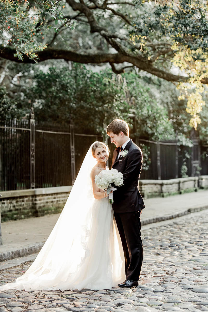 Bride and groom stand on the cobblestones of Washington Square, Charleston, South Carolina