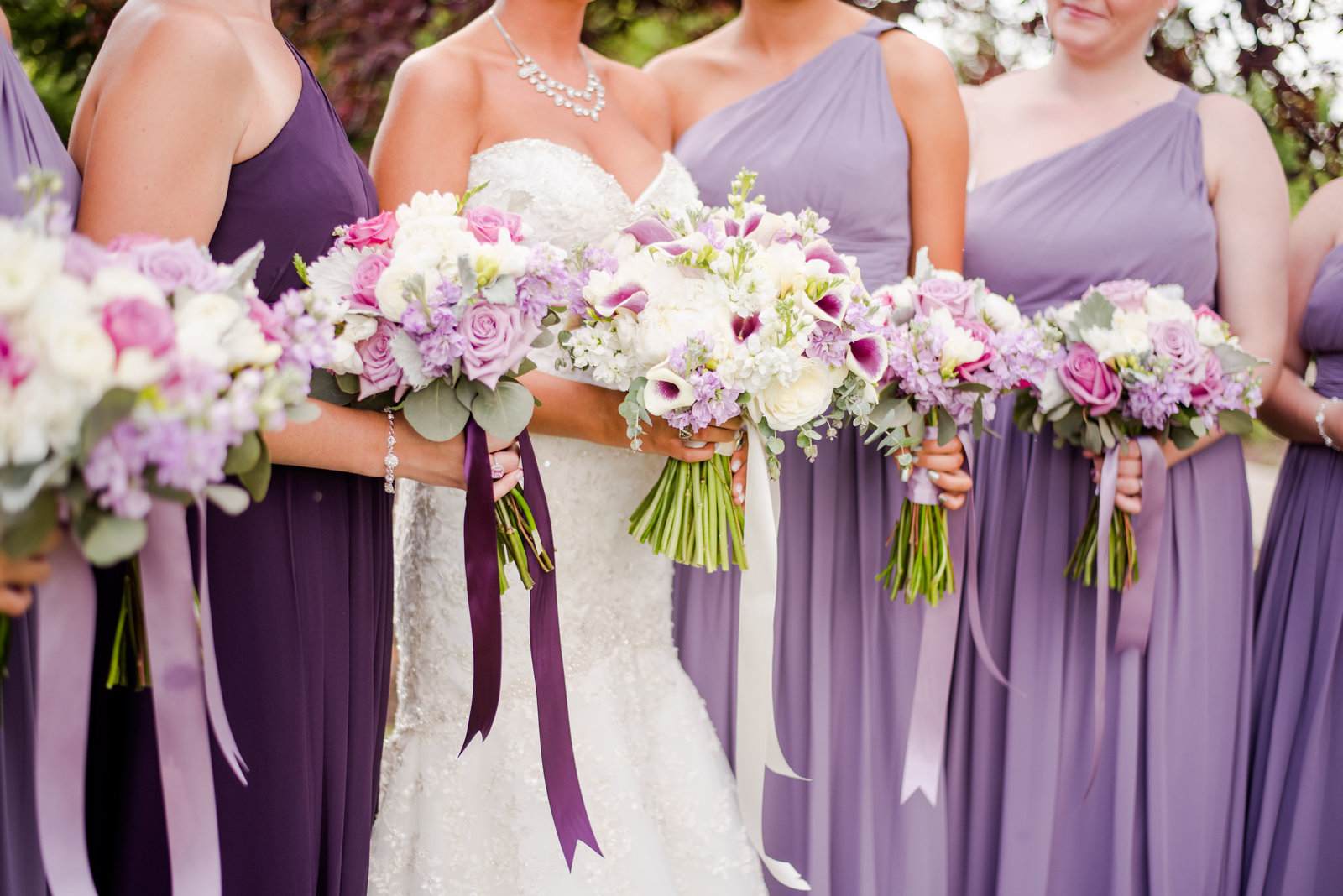 bride-standing-with-her-bridesmaids-holding-their-purple-bouquets