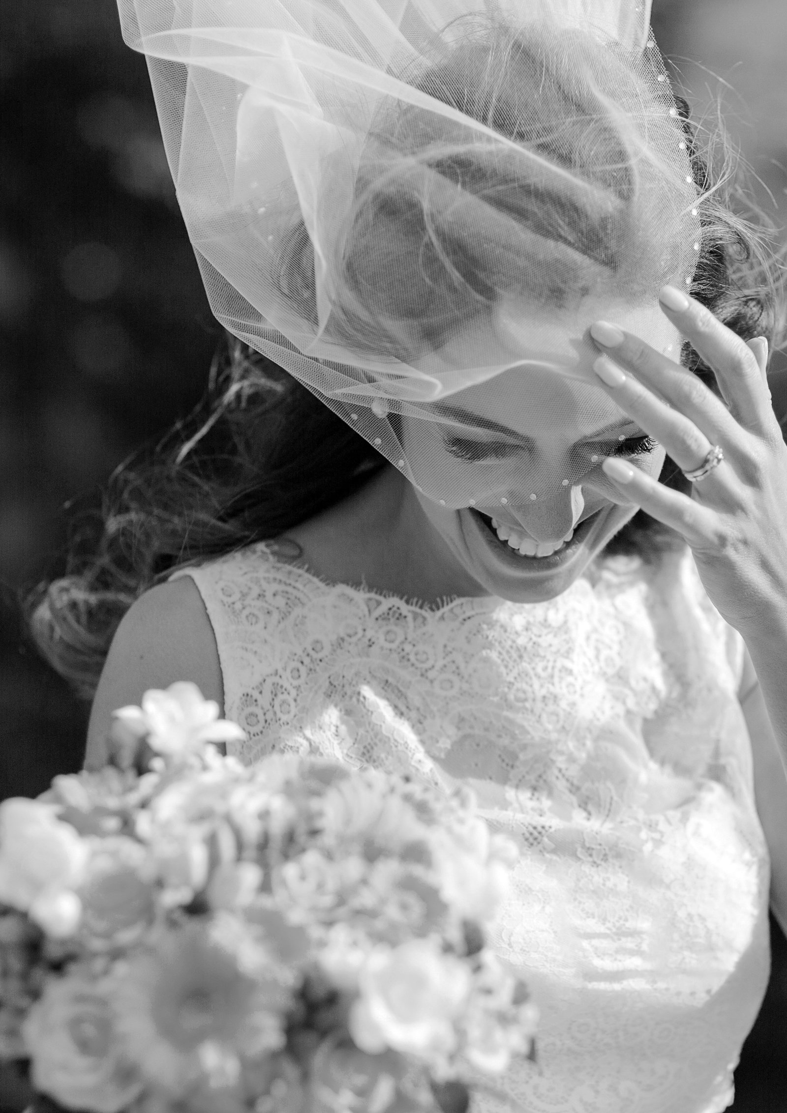 Black and white portrait wedding photo of bride laughing as her veil blows up in the wind on her wedding day