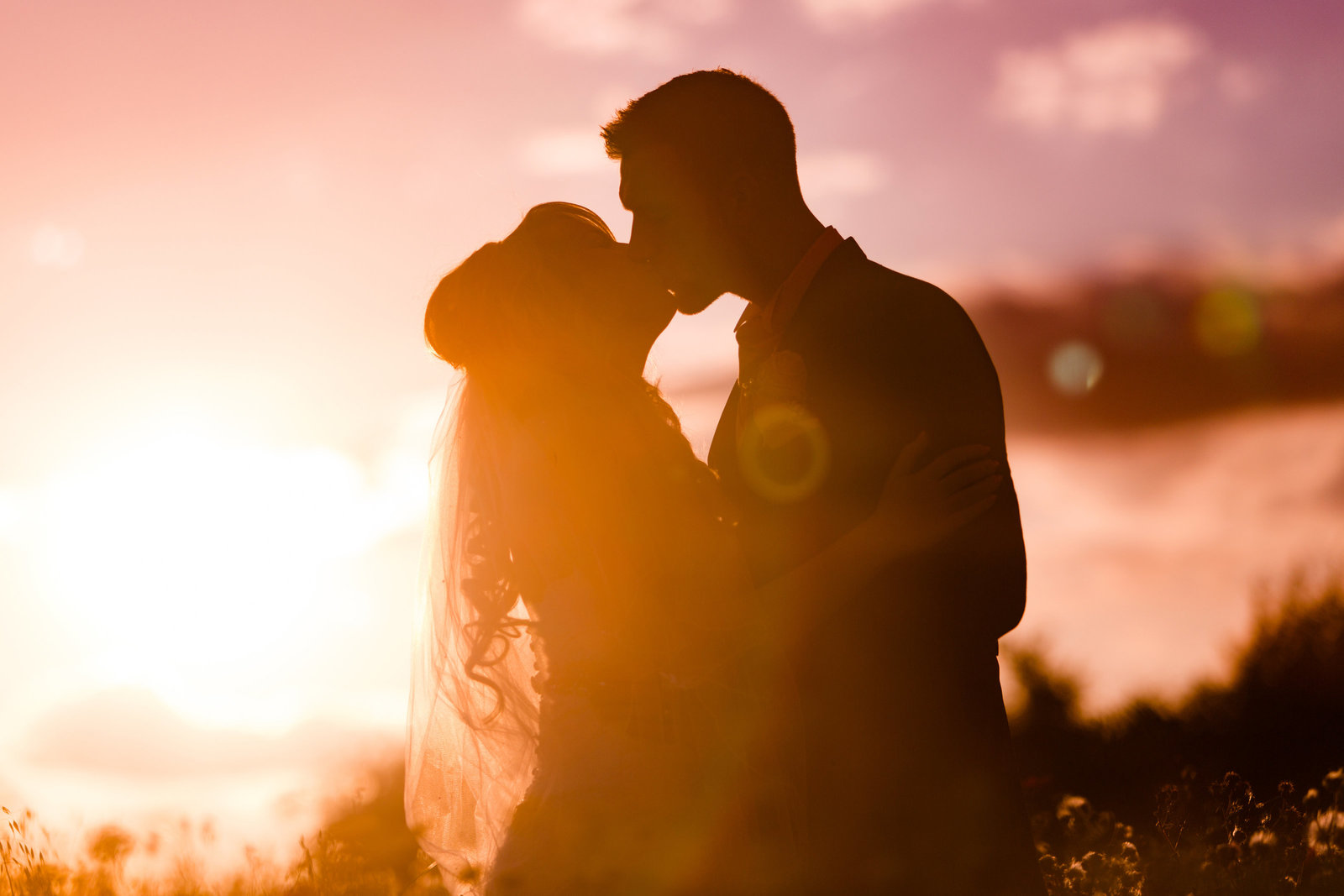 A beautiful silhouette of the bride and groom during romatic evening couple portraits at twilight, showing the stunning pink sunset set with sun flare in the fields taken by Adorlee at Southend Barns wedding venue.