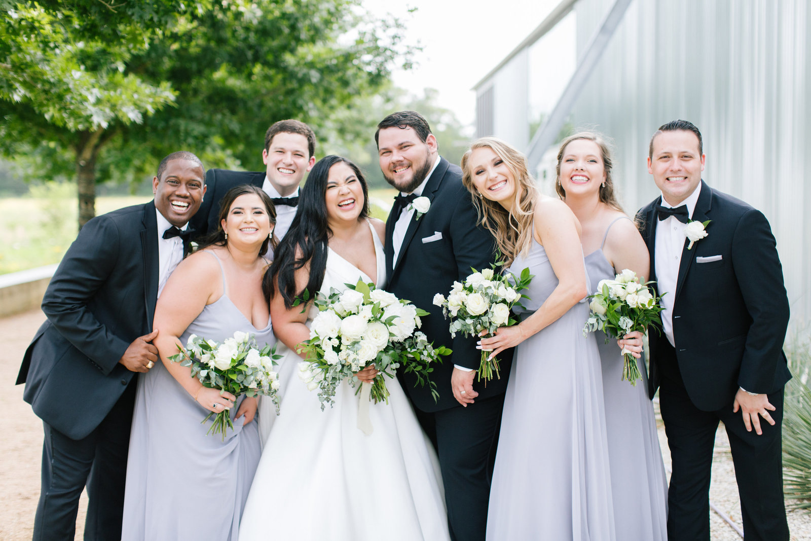 Outdoor wedding in Dripping Springs with white florals, tuxedos, and light grey bridesmaids dresses